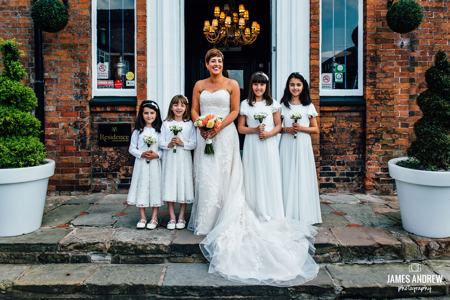 bridal party on stairs outside wedding venue