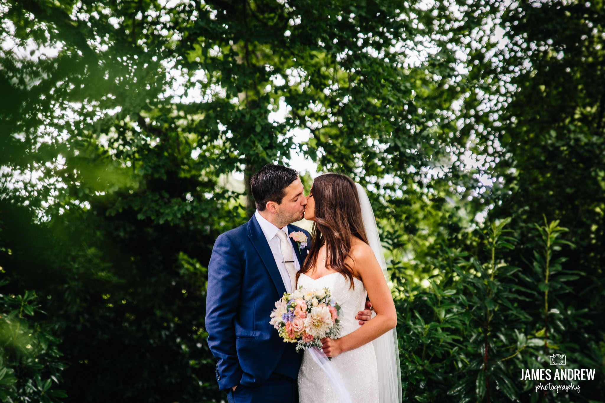 Bride And Groom Kissing In Green Woodland outdoors