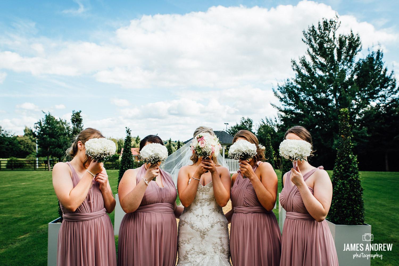Bridesmaids hide behind flowers