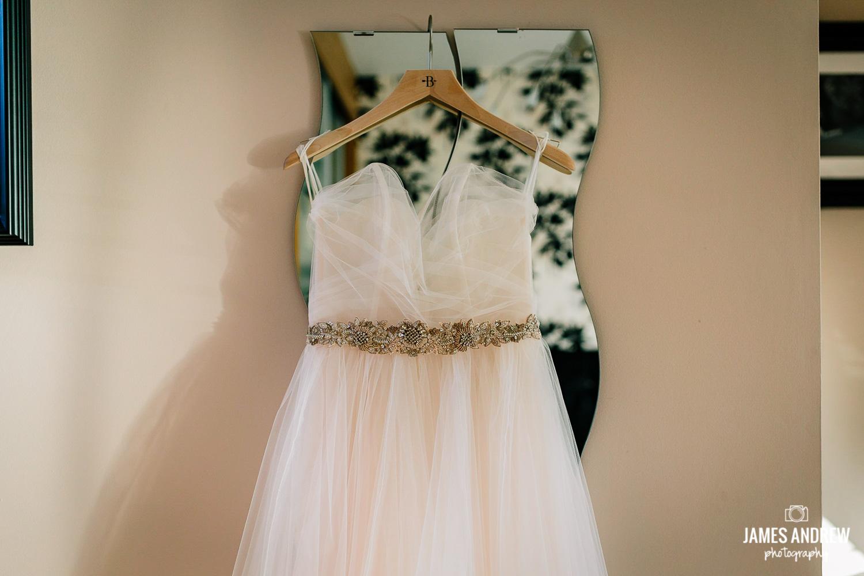 Wedding dress hanging above mirror