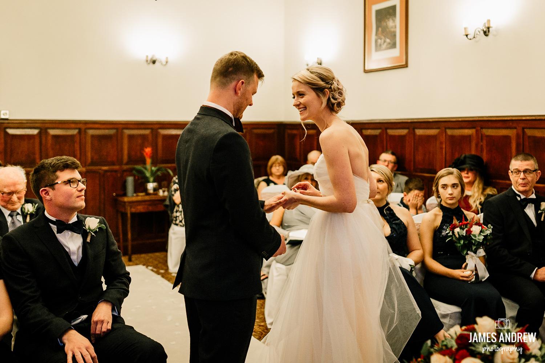 Bride pushing grooms wedding ring on