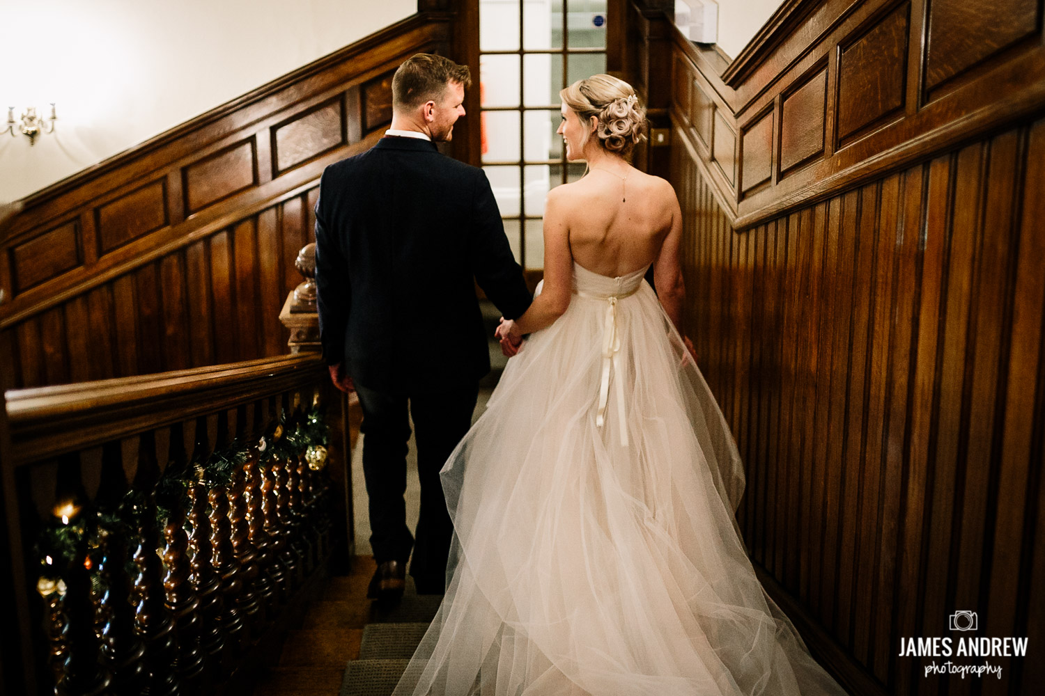 Bride and groom walk down stairs