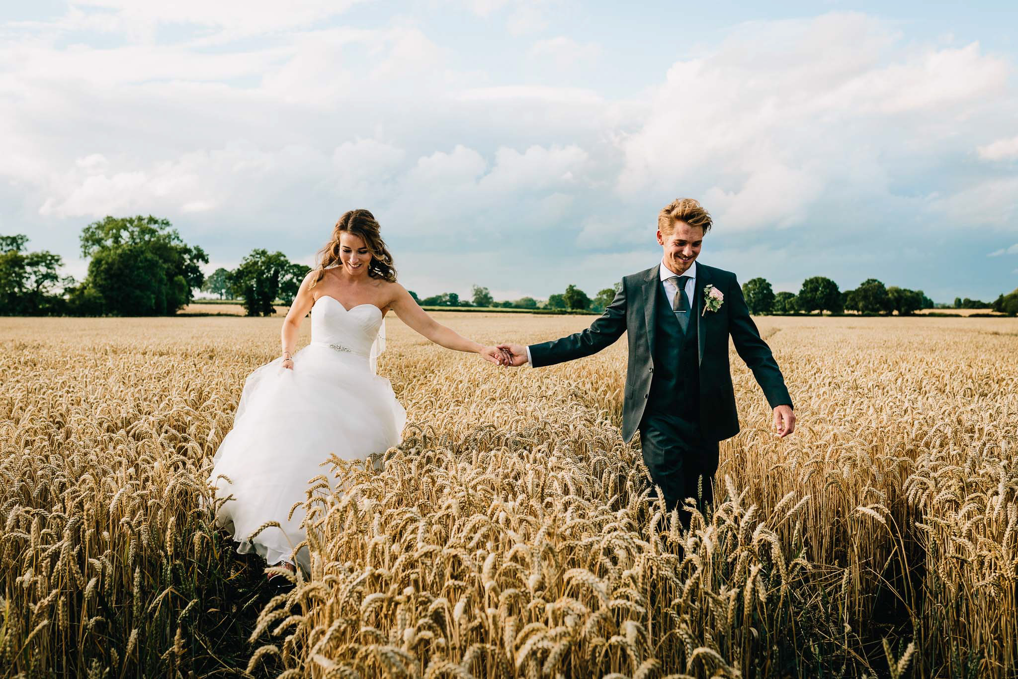 MARRIED COUPLE WALKING IN FIELD AT MYTHE WEDDING BARN STAFFORDSHIRE