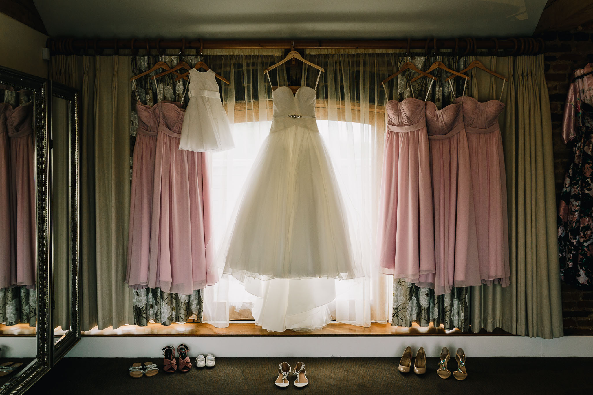 WEDDING DRESS AND BRIDESMAIDS DRESSES HANGING IN WINDOW WITH SHOES