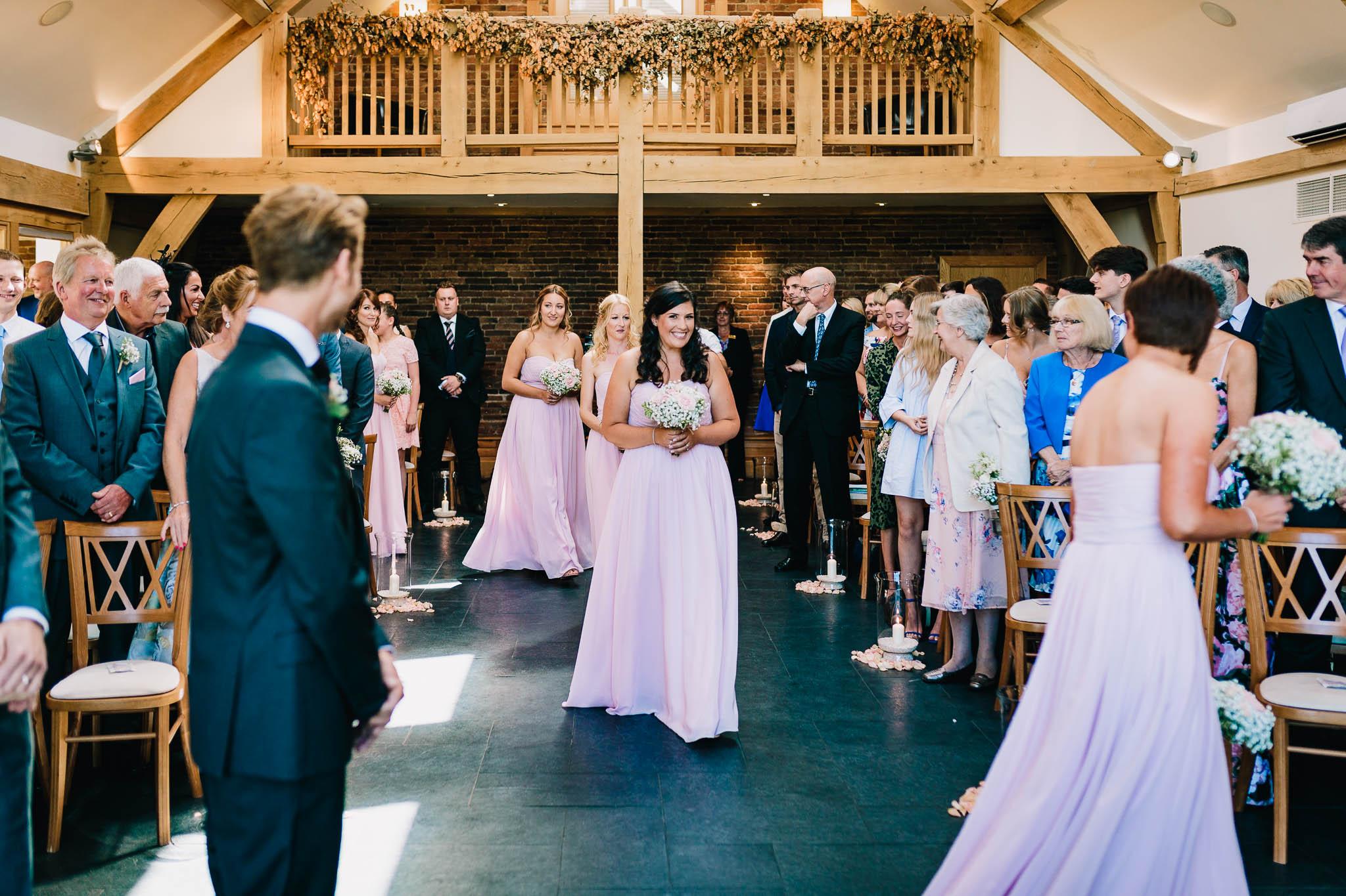 BRIDESMAIDS WALKING DOWN THE ISLE IN CHURCH