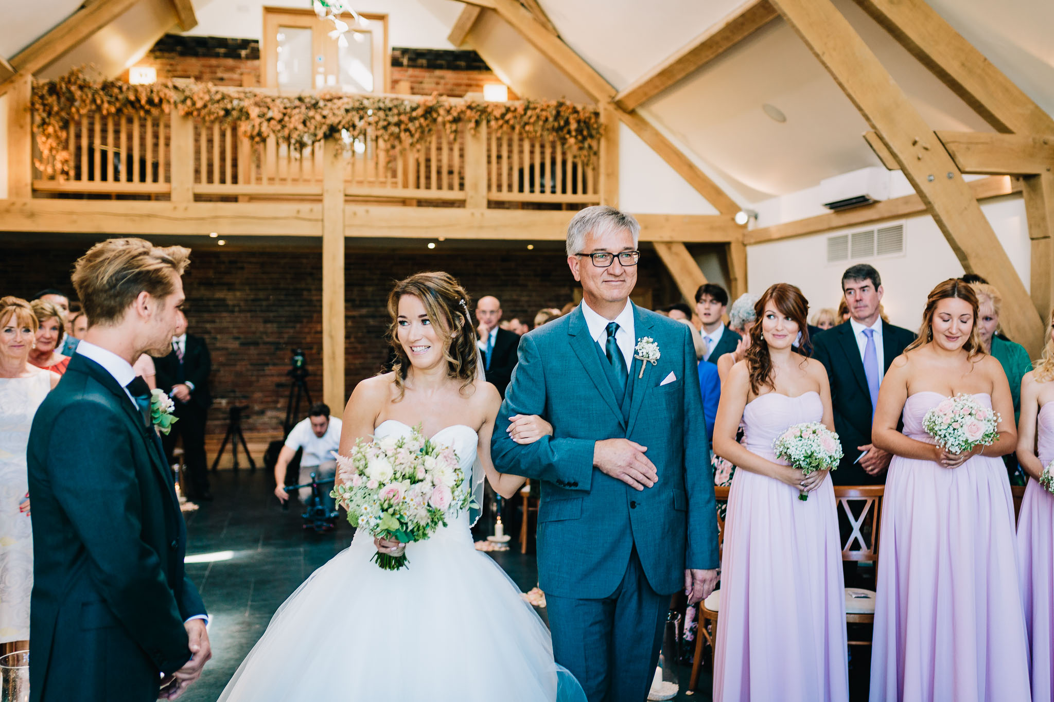 BRIDE AND DAD LOOKING AT GROOM IN CHURCH