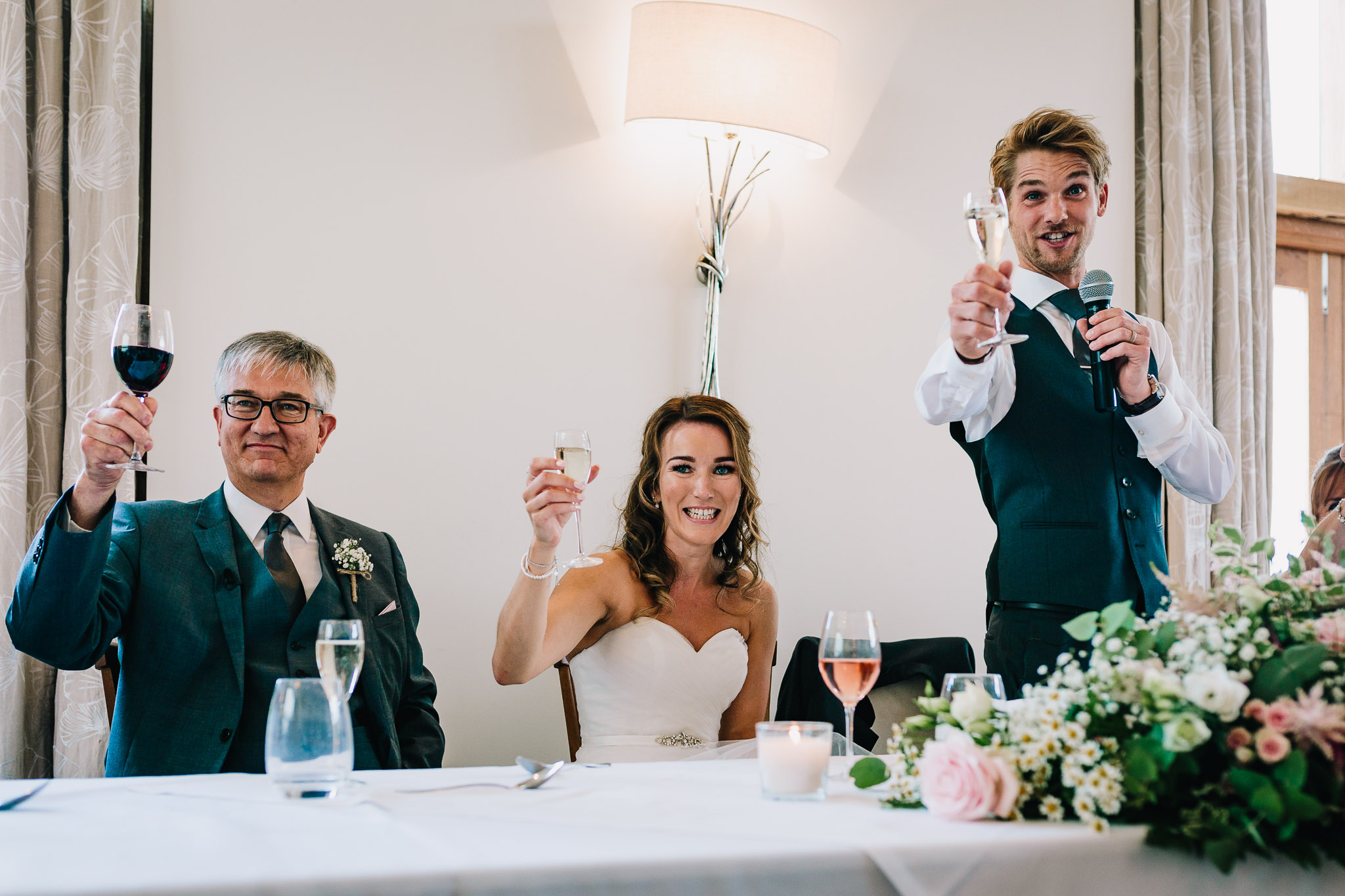 BRIDE AND GROOM TOASTING WITH CHAMPAGNE GLASSES CHEERS