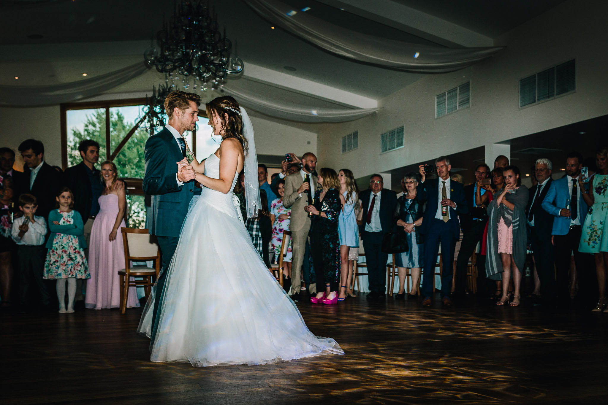 COUPLES FIRST WEDDING DANCE IN FRONT GUESTS ON DANCE FLOOR