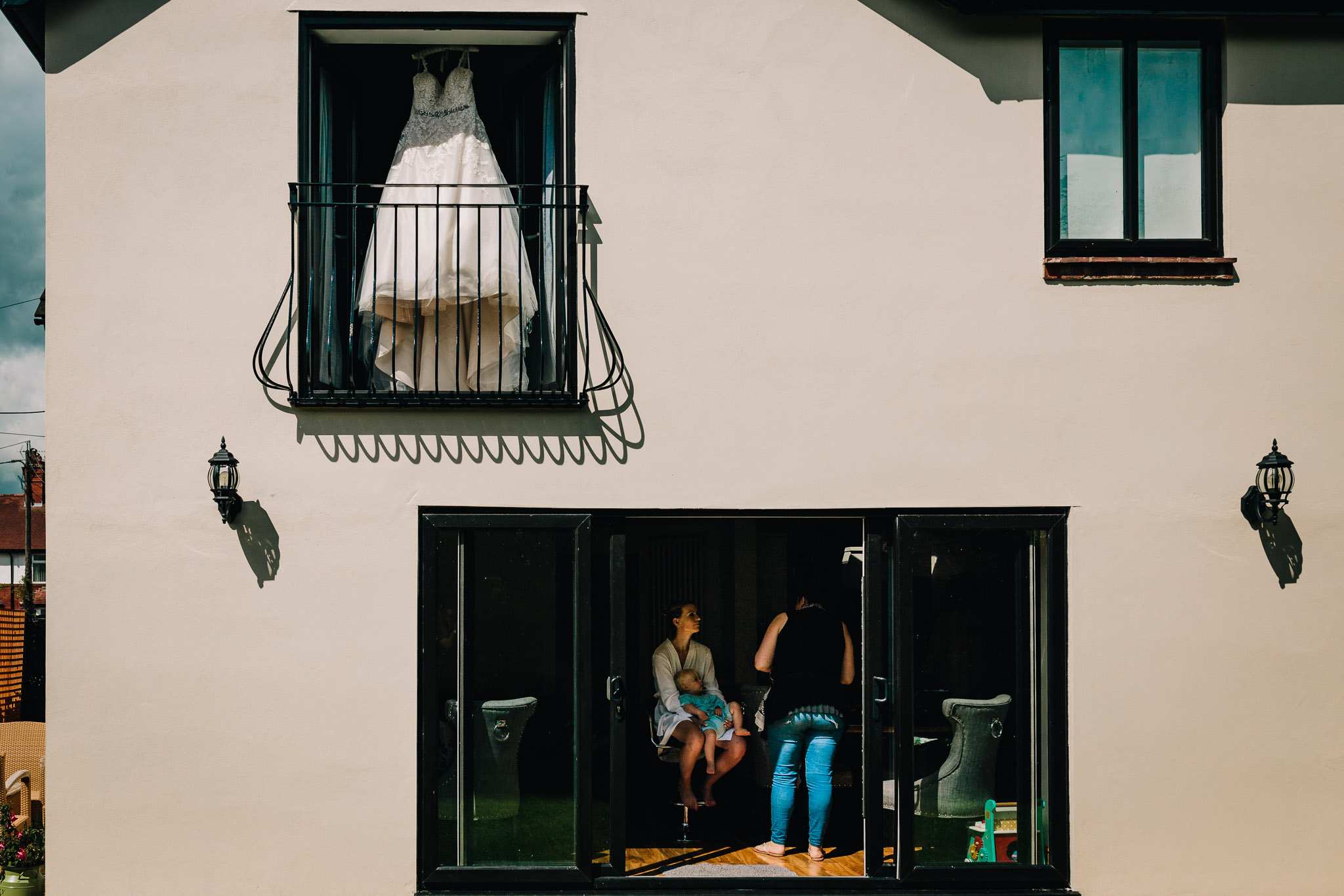BRIDE GETTING READY AT HOME DRESS HANGING IN UPSTAIRS WINDOW