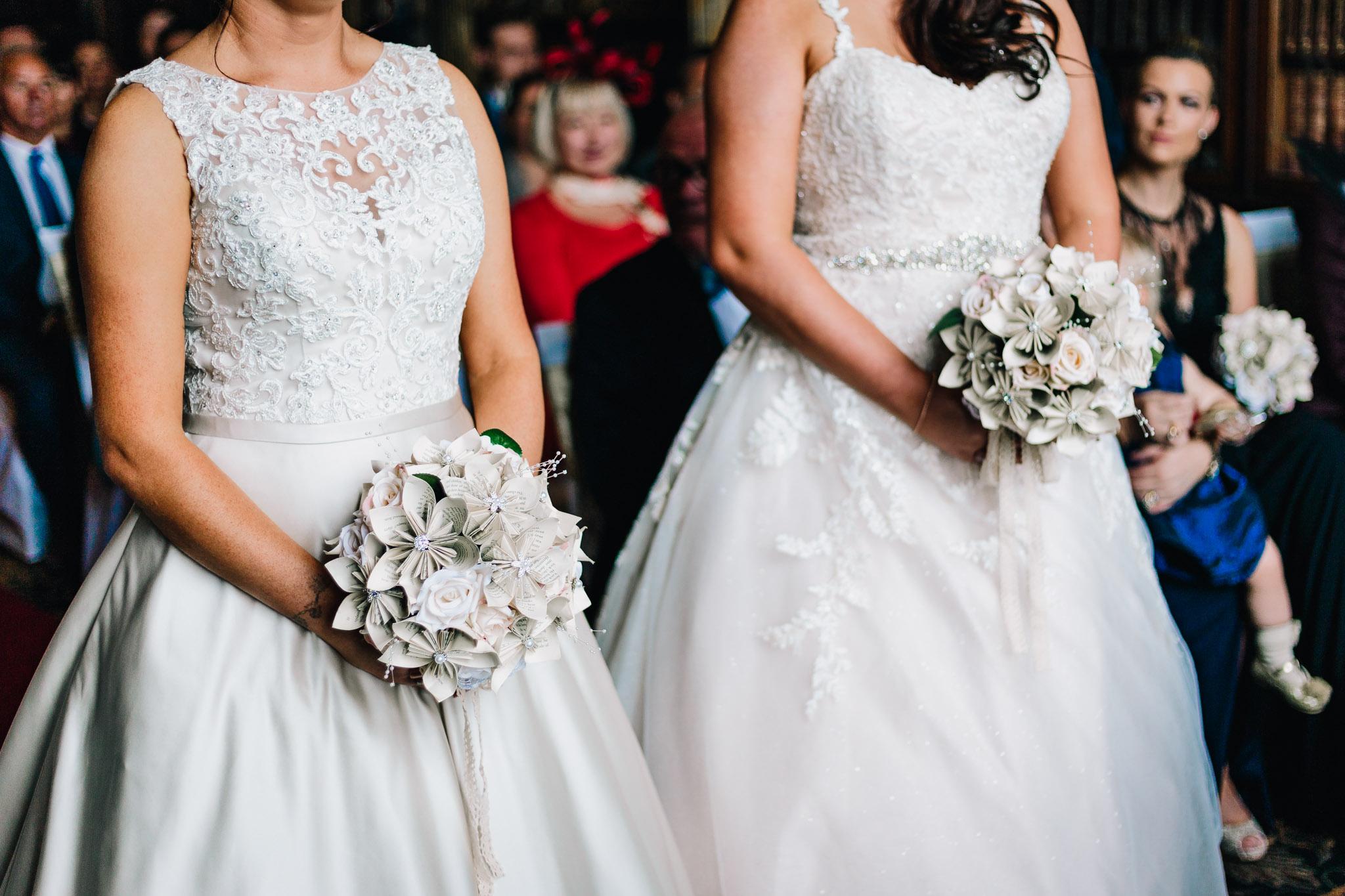SAME SEX BRIDES HOLDING HARRY POTTER PAPER FLOWERS AT WEDDING