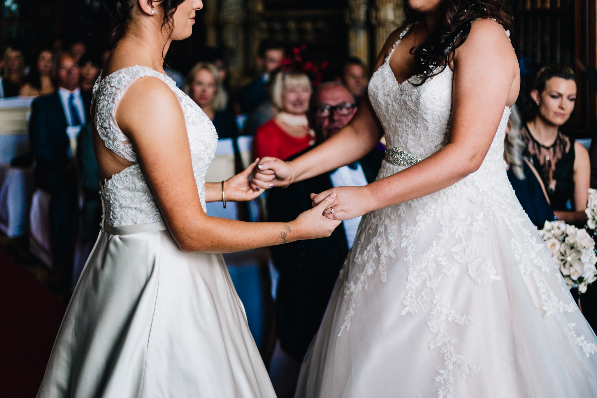 BRIDES HOLDING HANDS AT WEDDING CEREMONY