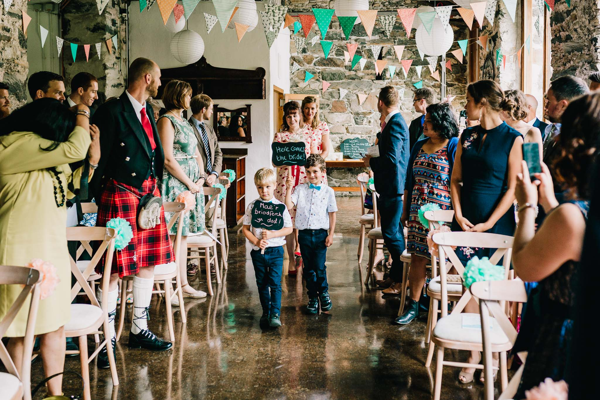 YOUNG WEDDING GUESTS WALKING DOWN THE ISLE BEFORE BRIDE ENTERS BARN