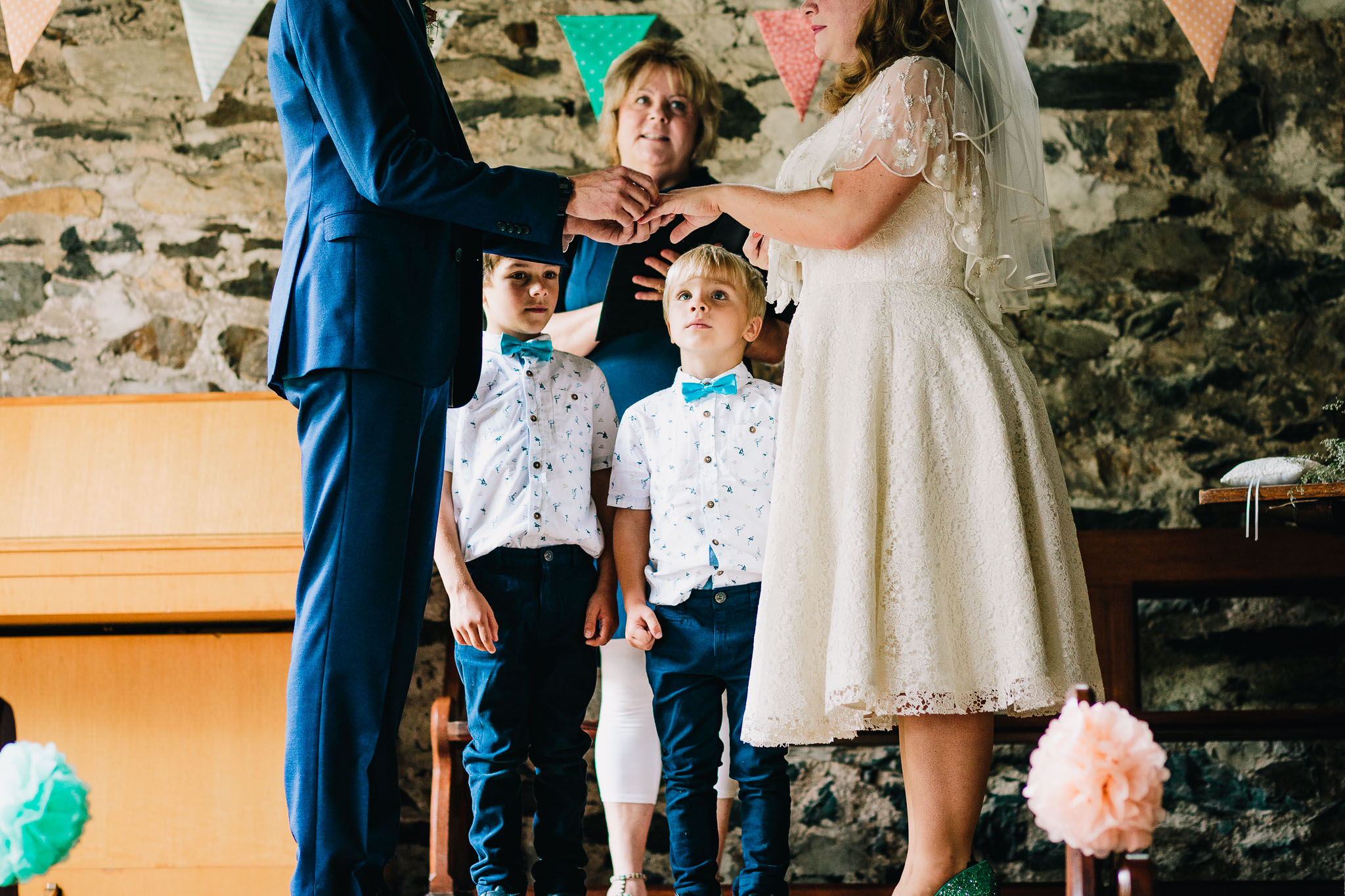 BOY LOOKING UP AT BRIDE PUTTING WEDDING RING ON GROOMS FINGER
