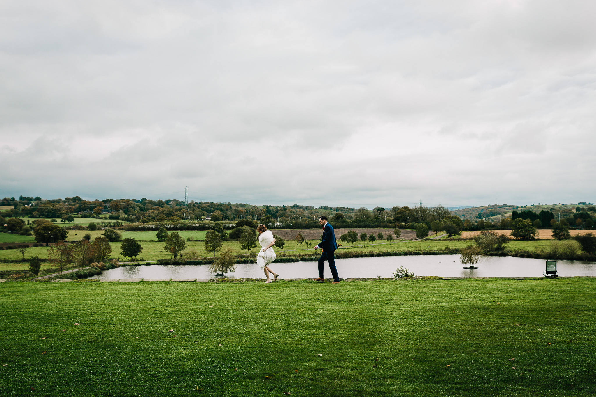 BRIDE AND GROOM WALKING PAST COUNTRY HOUSE
