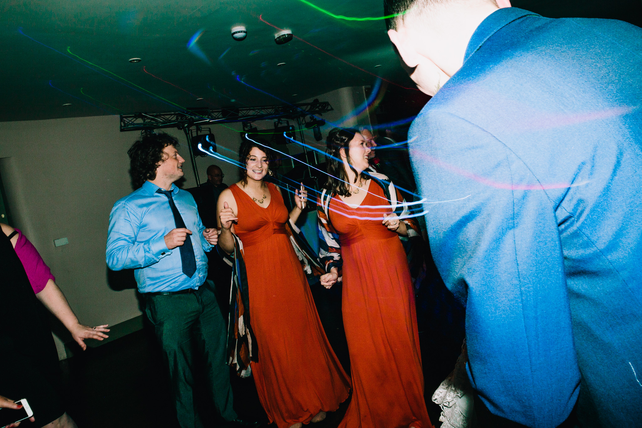 WEDDING GUESTS DANCE AT EVENING RECEPTION PARTY
