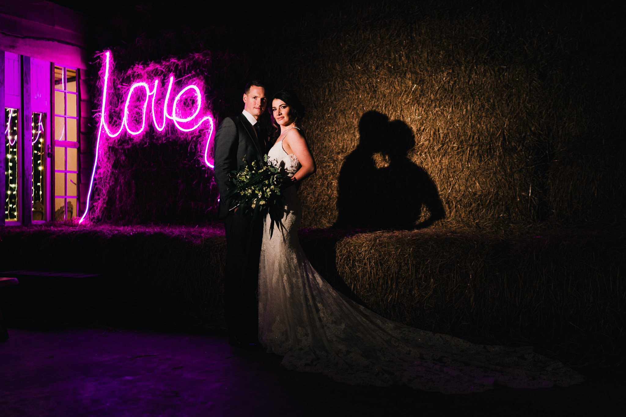 creative flash picture of married couple by hay bales at owen house barn staffordshire and cheshire