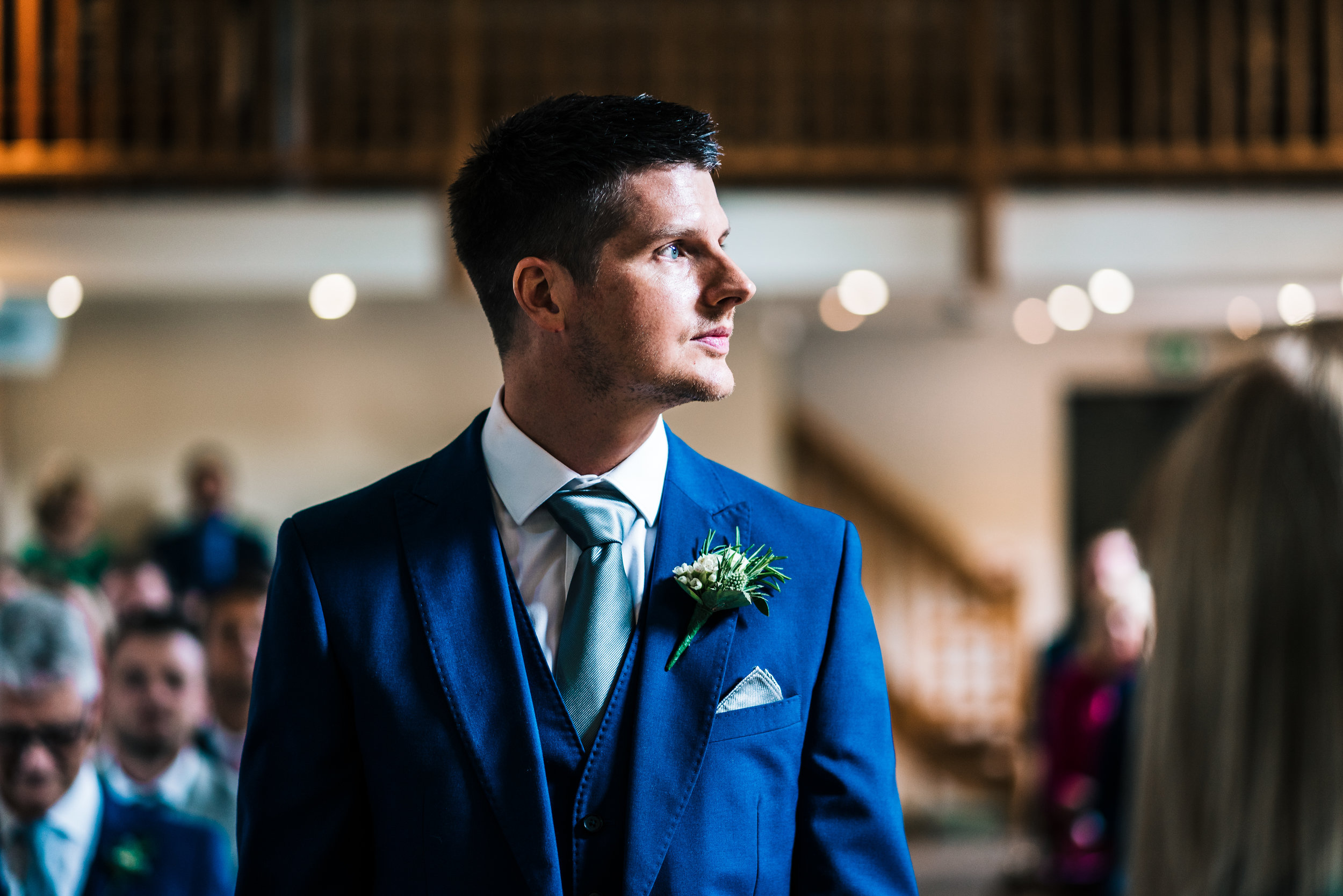 GROOM WAITING FOR BRIDE TO COME DOWN THE ISLE AT THE ASHES