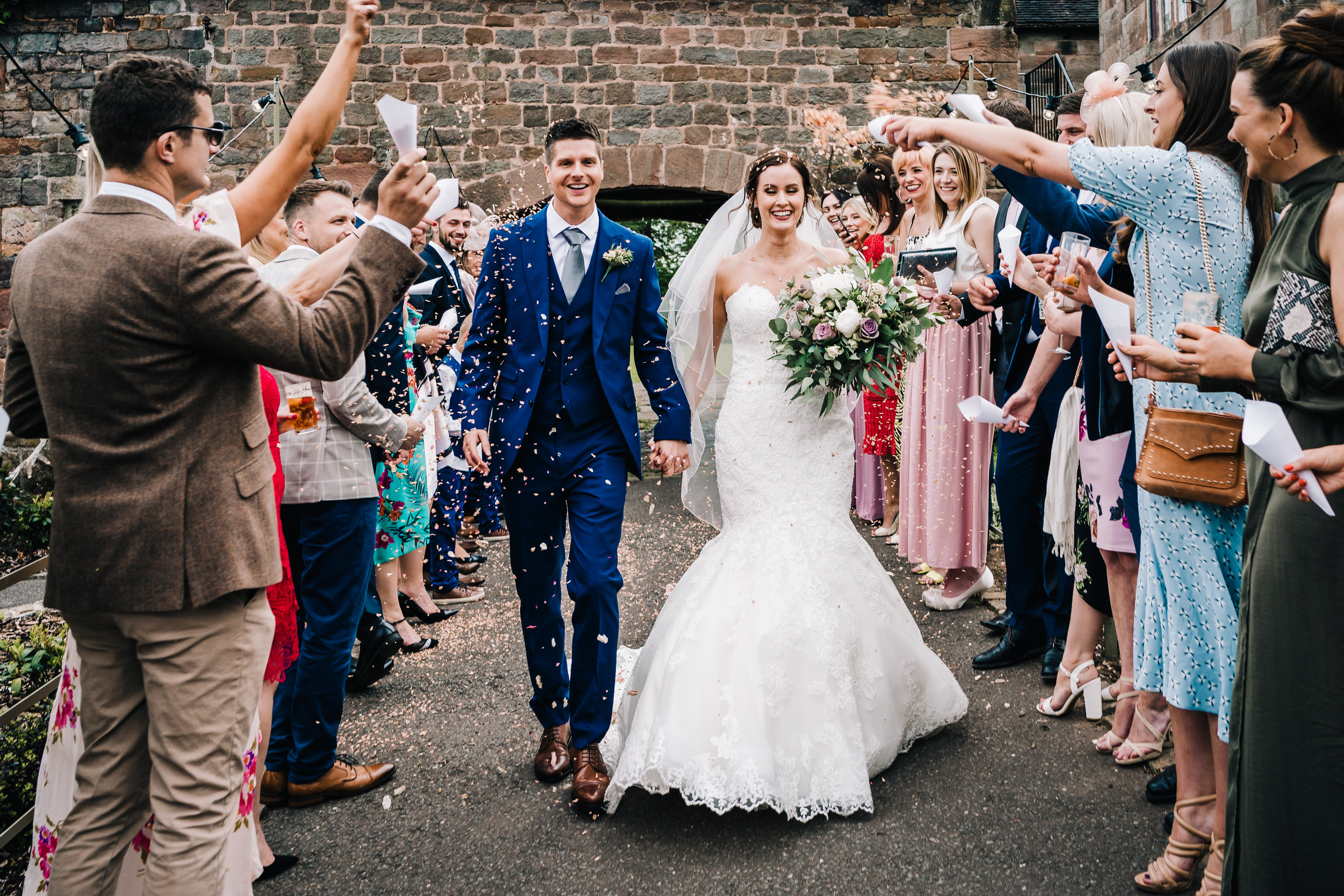 WEDDING COUPLE WALKING TOGETHER THROUGH CONFETTI AT THE ASHES