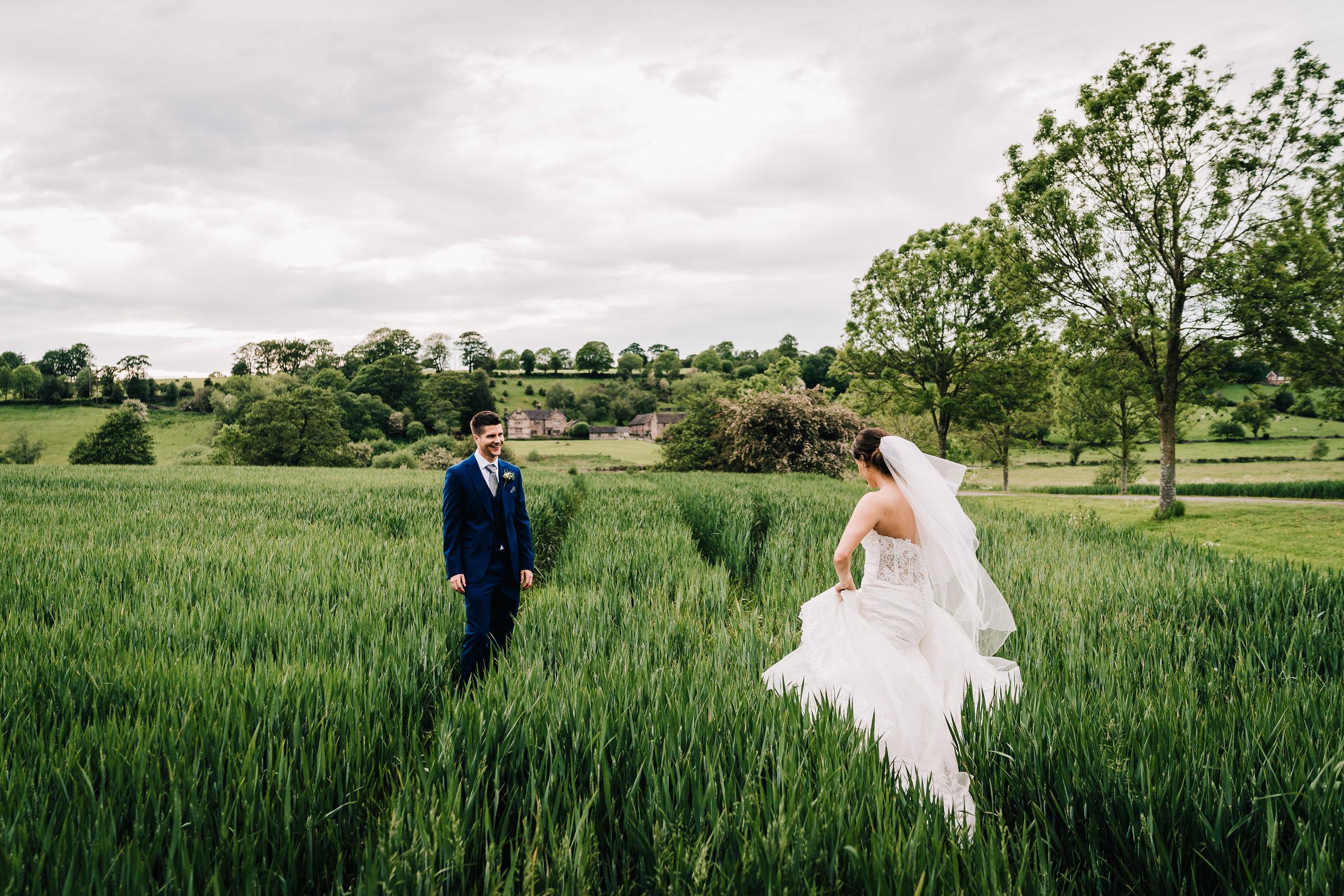 BRIDE AND GROOM IN FIELD DARK GREENS