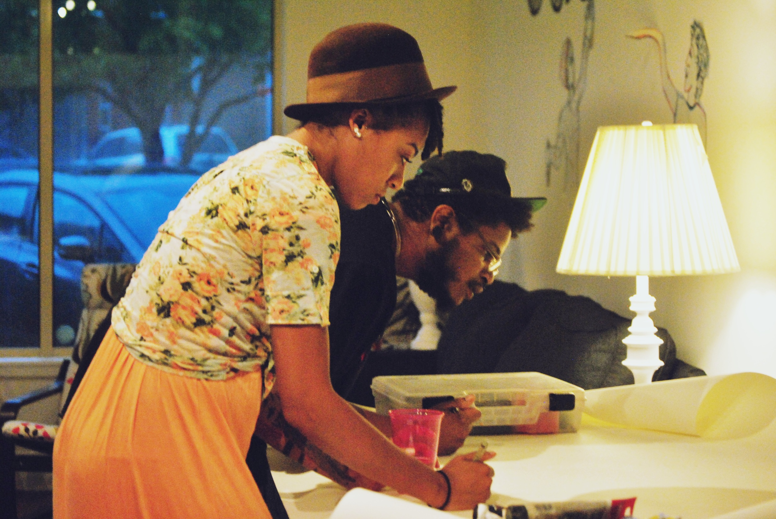 "Tiffany and LaDarrell lay down the first lines and colors for the ""Coloring Scroll"" table at our ""Mixed Medi-Us"" event at Causeway. Photo by Jequise Beverly."