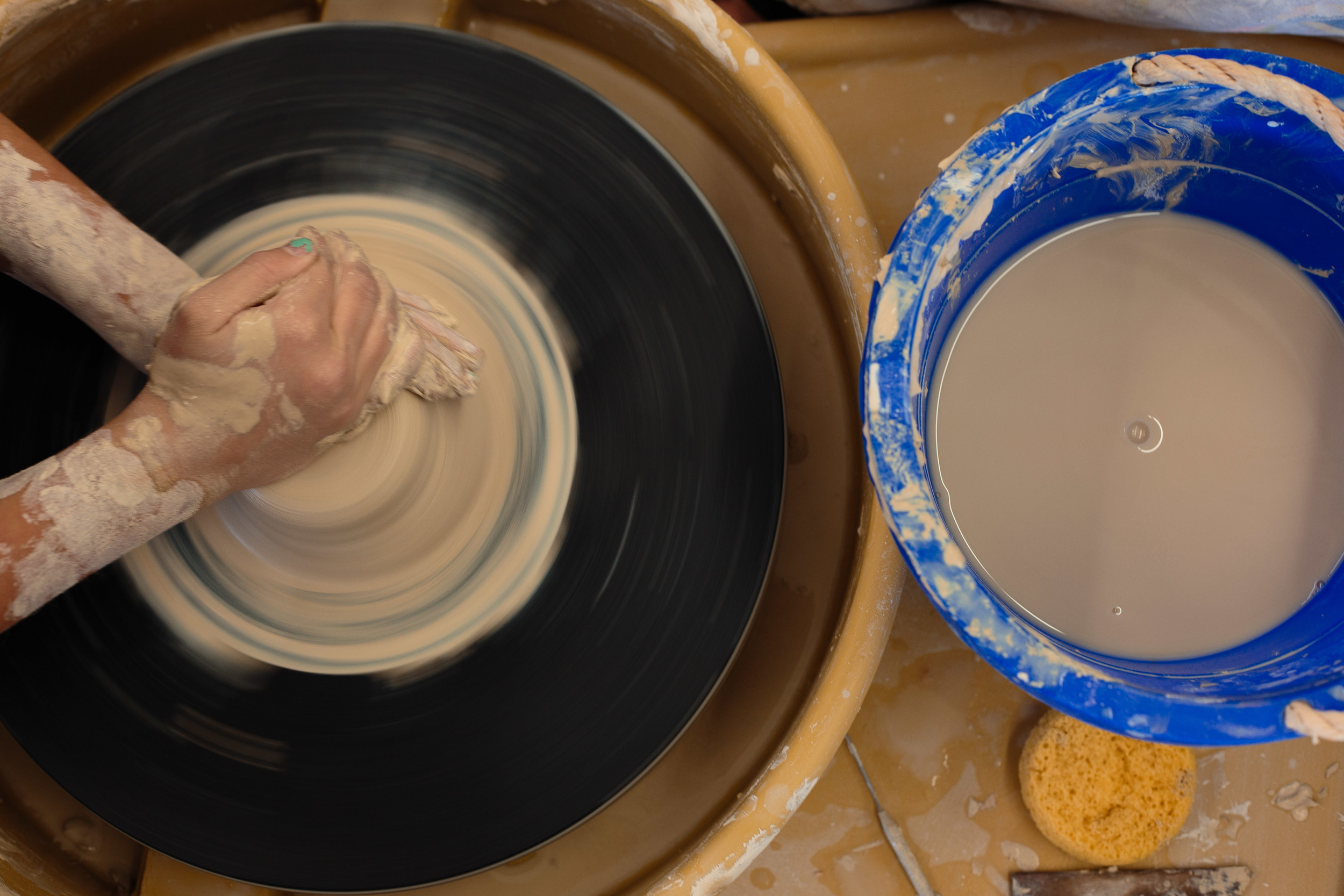 Artist Potter working pottery wheel throwing clay pot