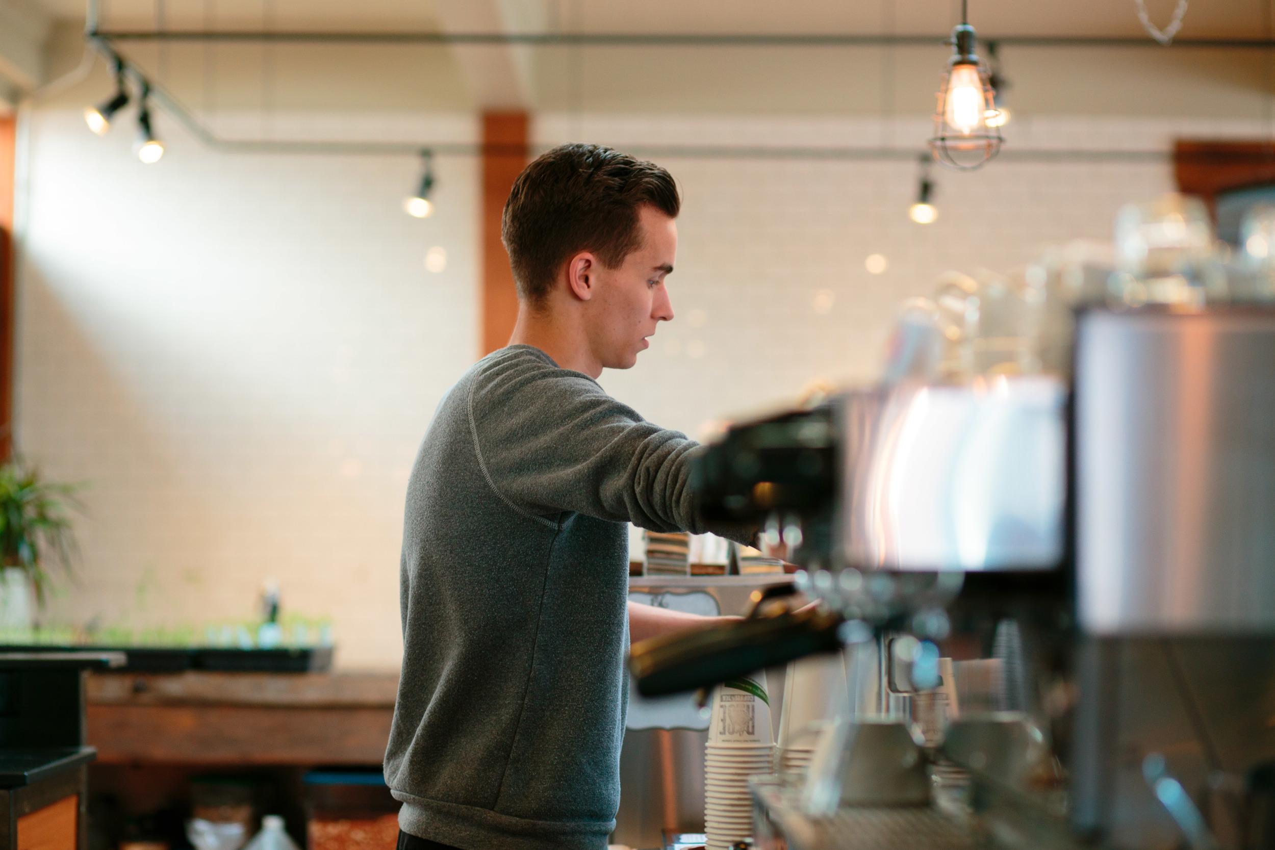 Barista behind espresso bar shop local coffee