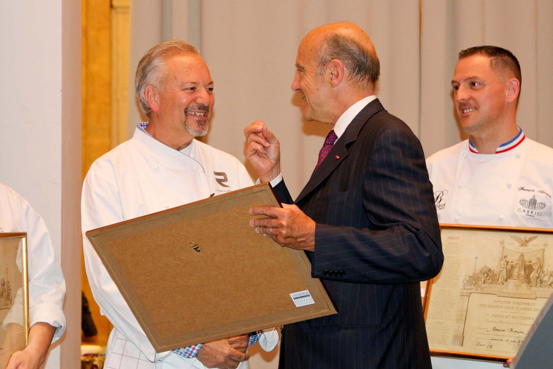CHEF OF NOTE JOHN SEDLAR AND FRANÇOIS ADAMSKI BEING PRESENTED WITH THE DIPLOME D'HONNEUR DES GRANDS CRUS FROM MAYOR ALAIN JUPPÉ.