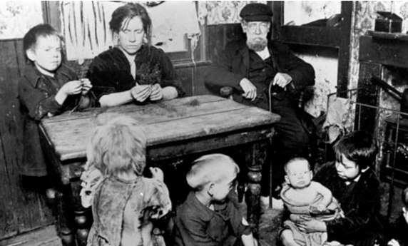 A lower class family in the Victorian period in their home. Look at the boy looking straight into the camera; that is not the face of a carefree child.