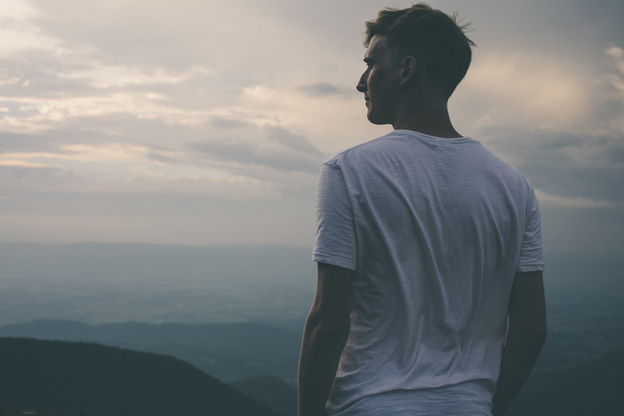 man-overlooking-mountains-thinking-about-success