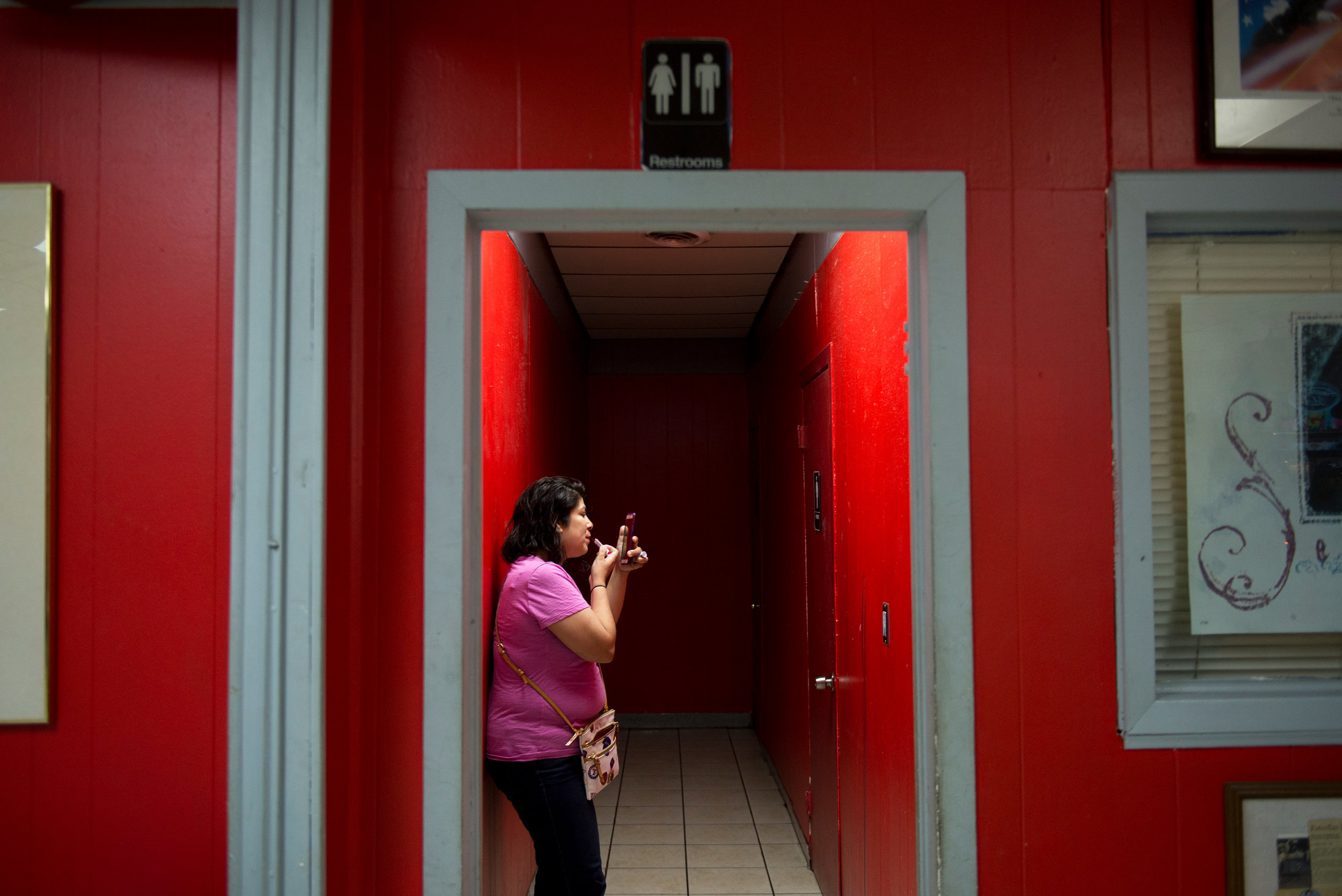 """A woman checks herself with her phone's camera, applying lipstick before an event celebrating the legacy of the """"Queen of Tejano,"""" Selena Quintanilla, at Country Burger in Oak Cliff on Saturday, March 25, 2017."""
