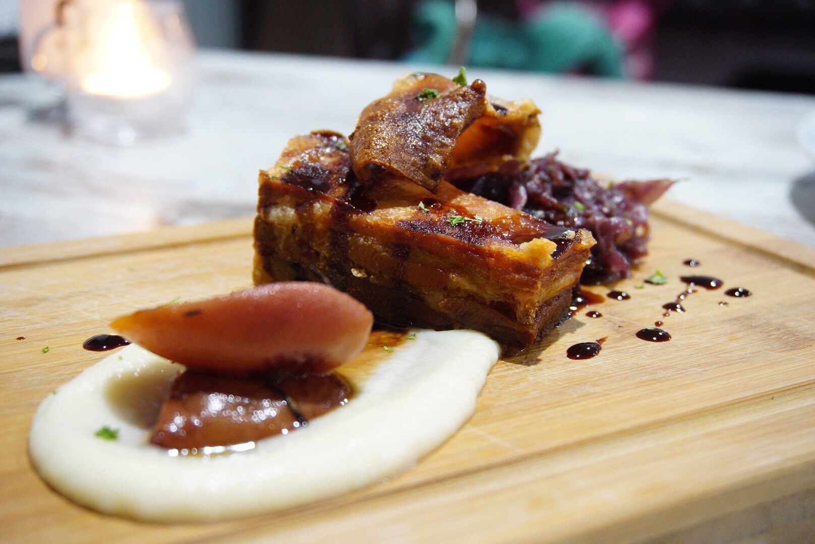 Roast pork belly with cauliflower puree, braised red cabbage and pulled pork croquette