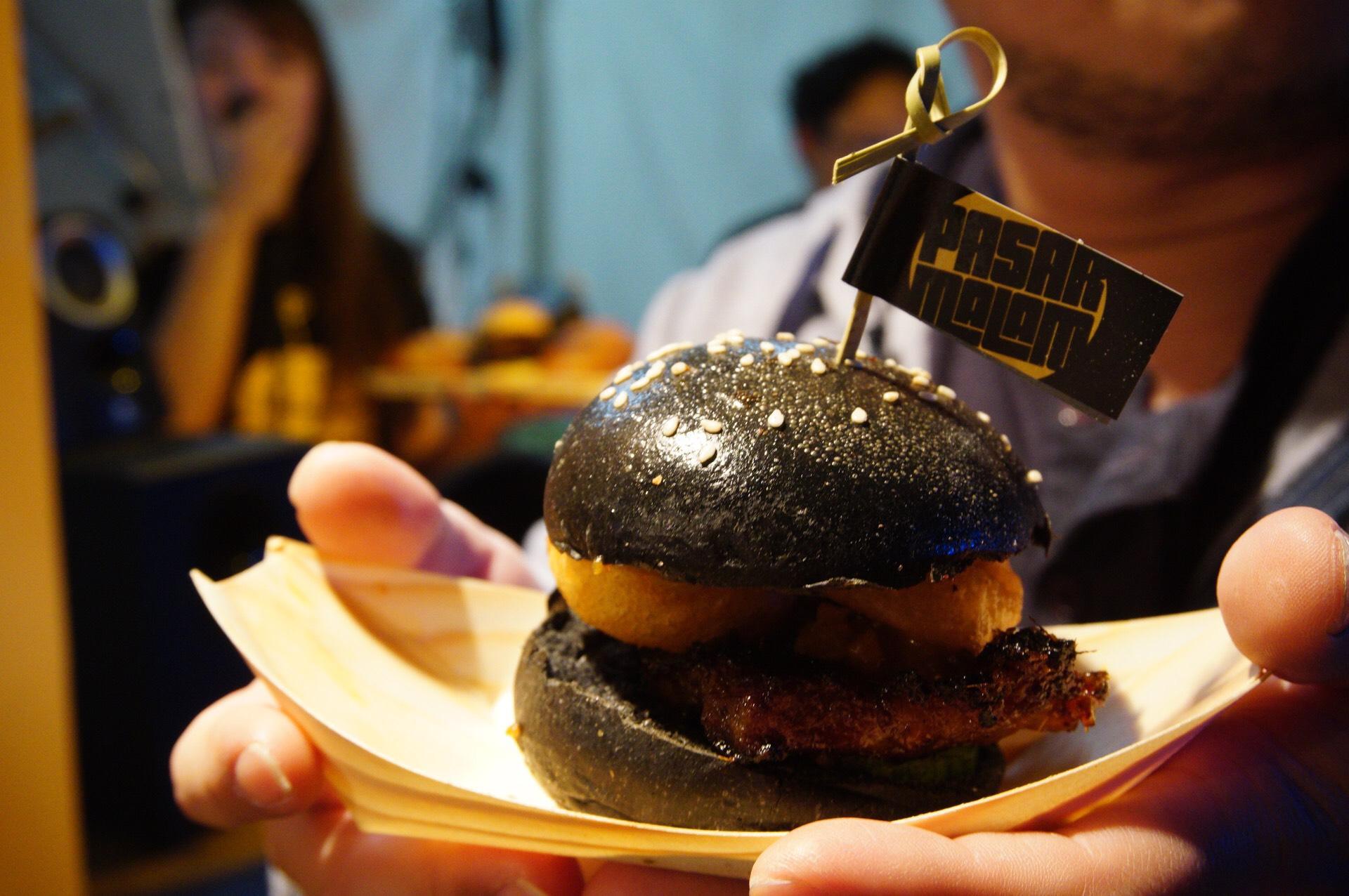 POrk BElly slider has onion rings, cucumber, peanut sauce, sandwiched in charcoal brioche bun