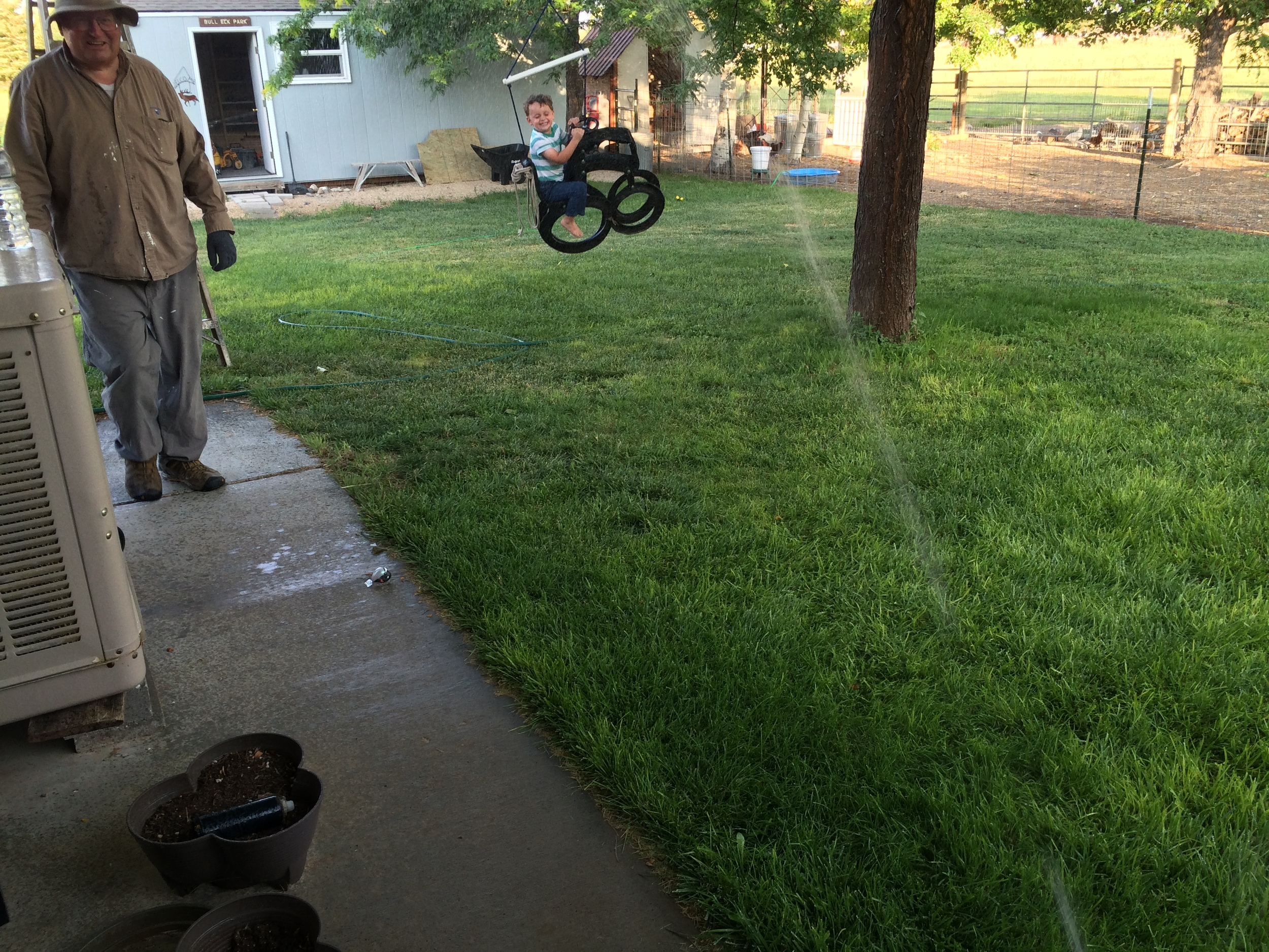Grandpa moved the swing and adjusted the sprinkler to spray Asher as he swung. Asher was a very good sport!