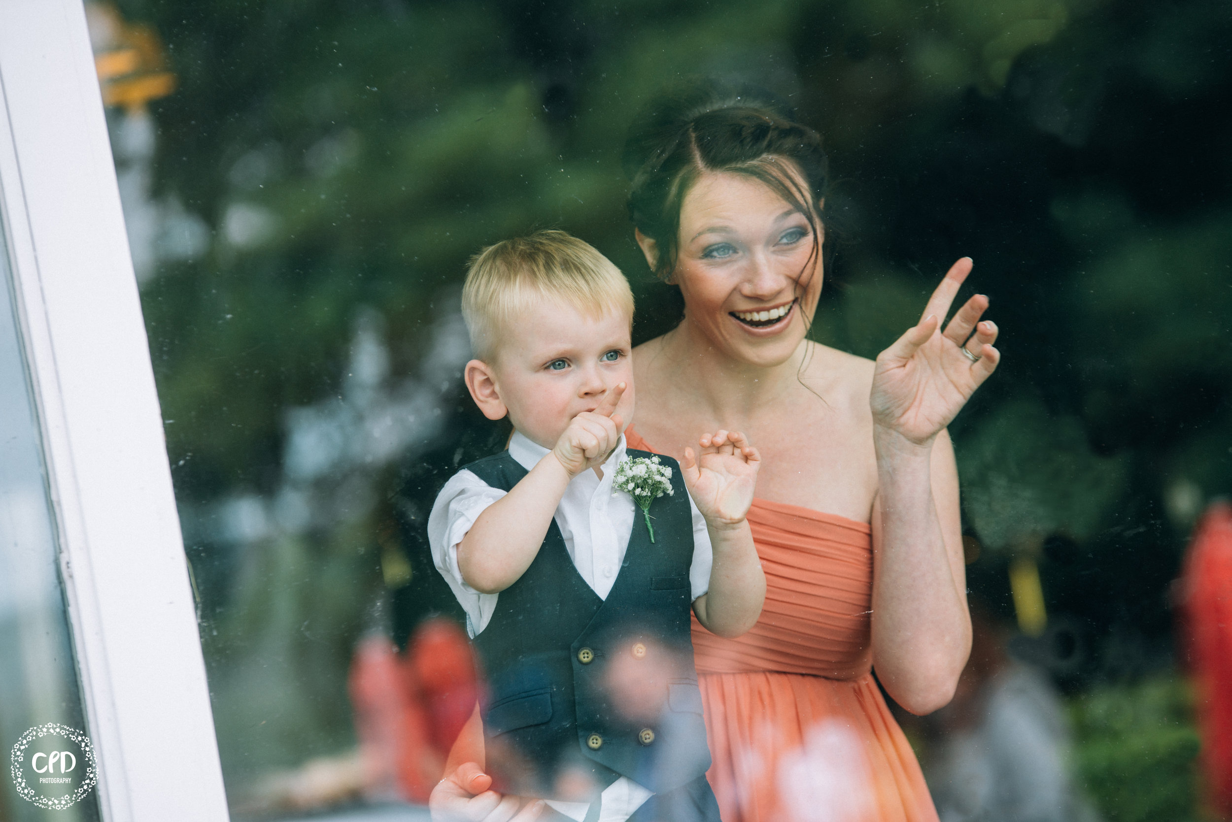 A Bridesmaid and Pageboy looking through a window