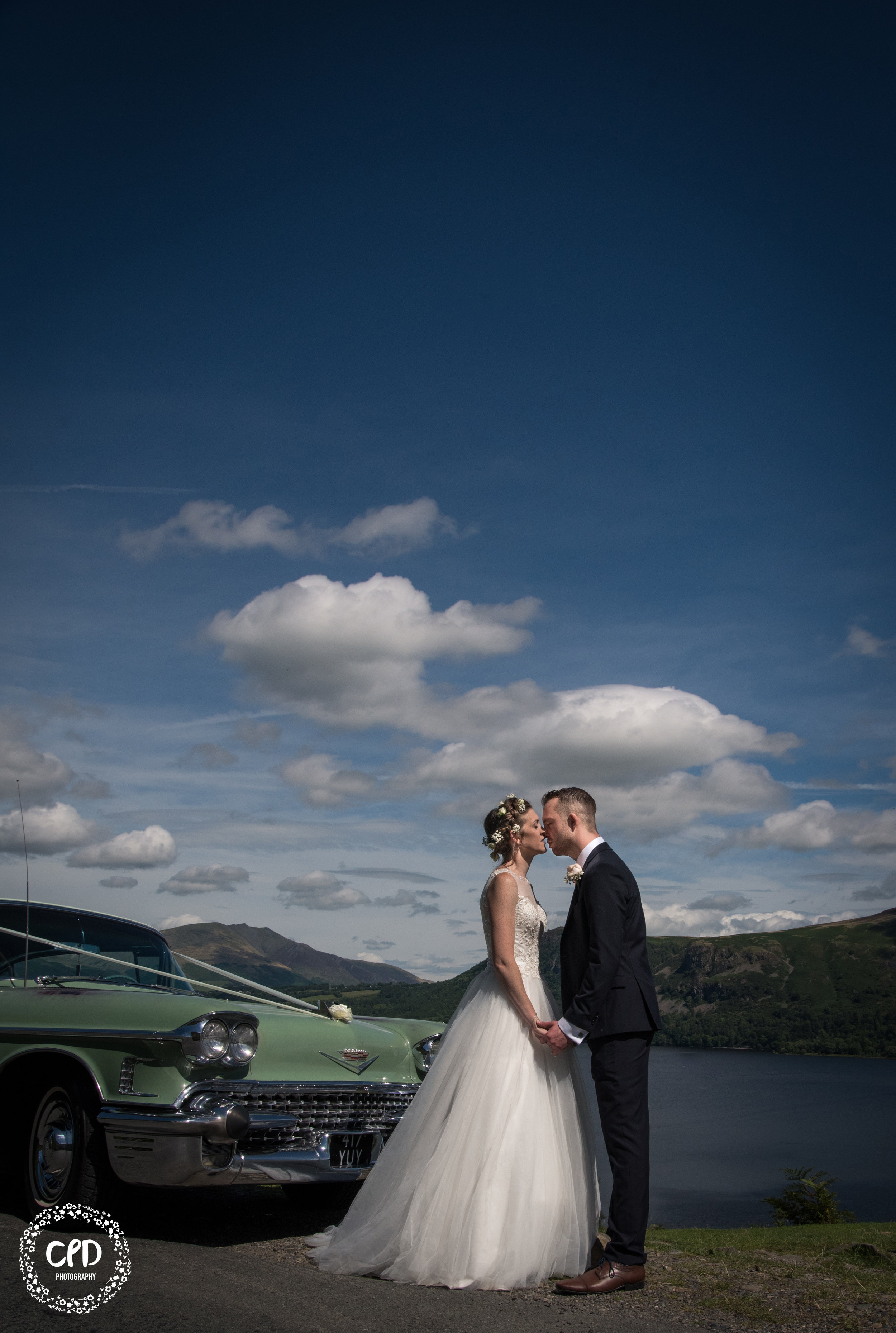 Bride and Groom Kissing in front of the cadillac