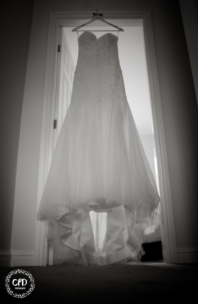 Bridal gown hanging in a doorway