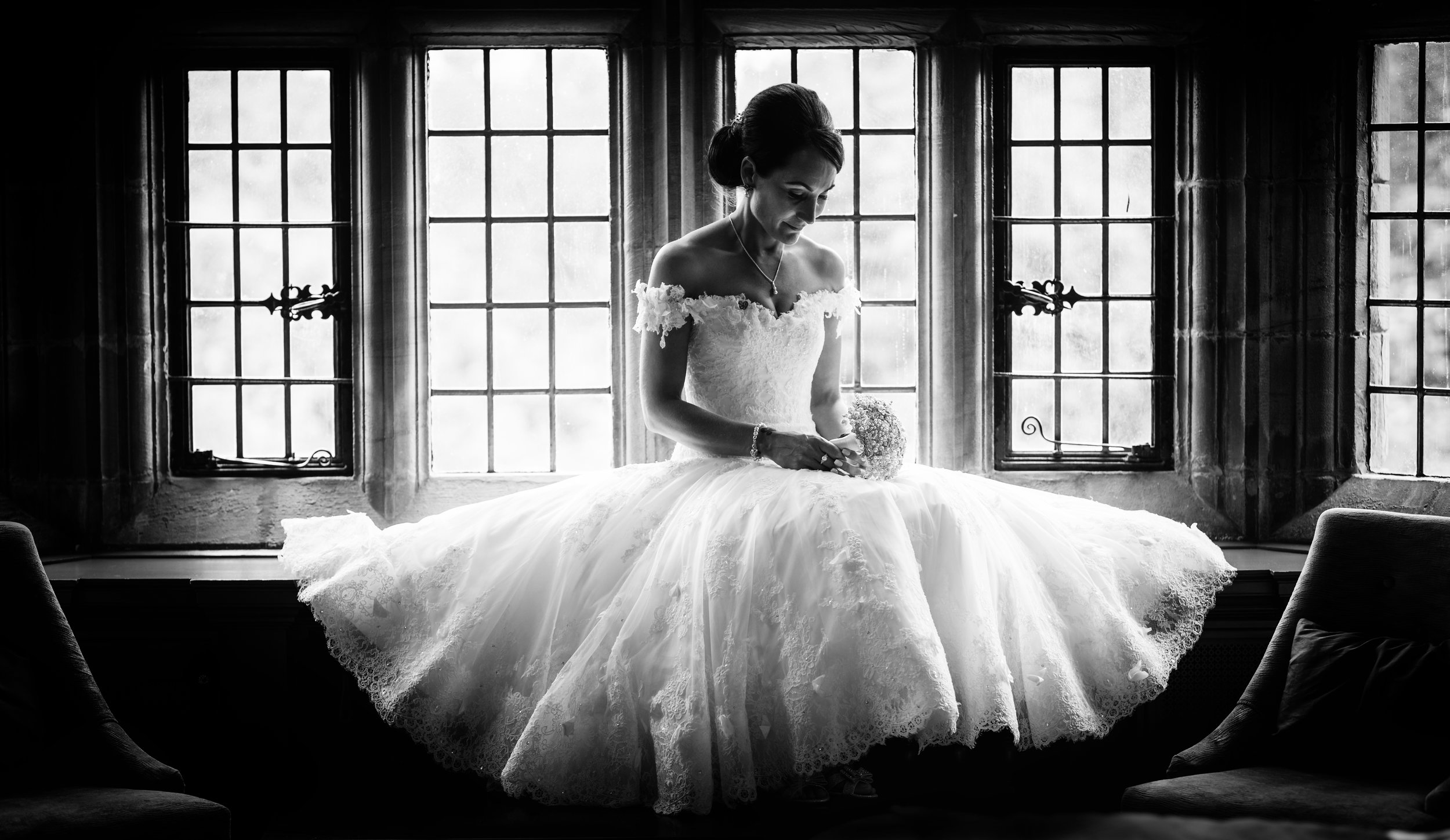 Black and White portrait of a bride sitting in a window seat