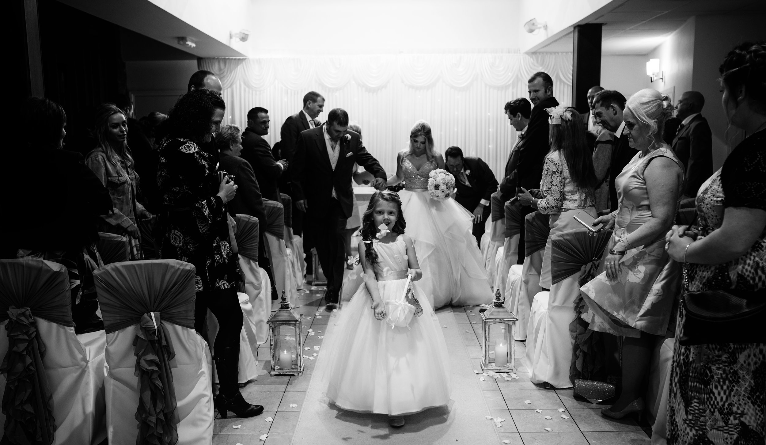 Flower girl sprinkling flowers during the happy couples exit