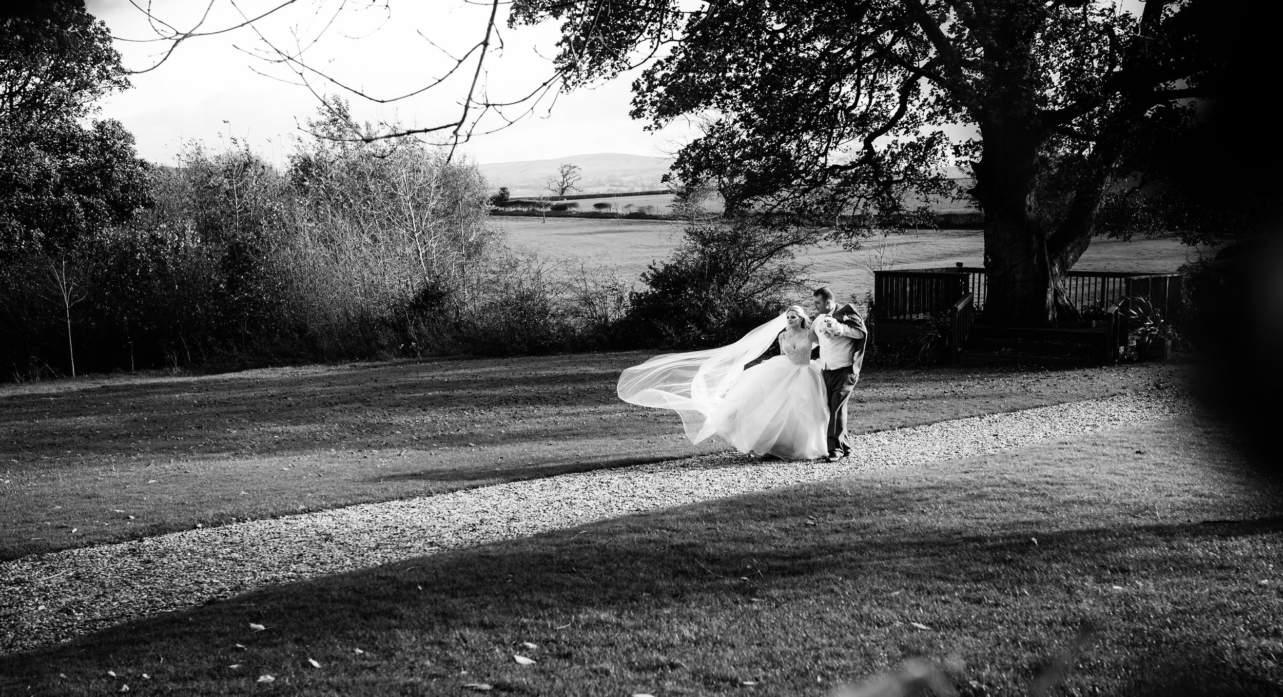 Black and white image of the bride and groom walking in the garden