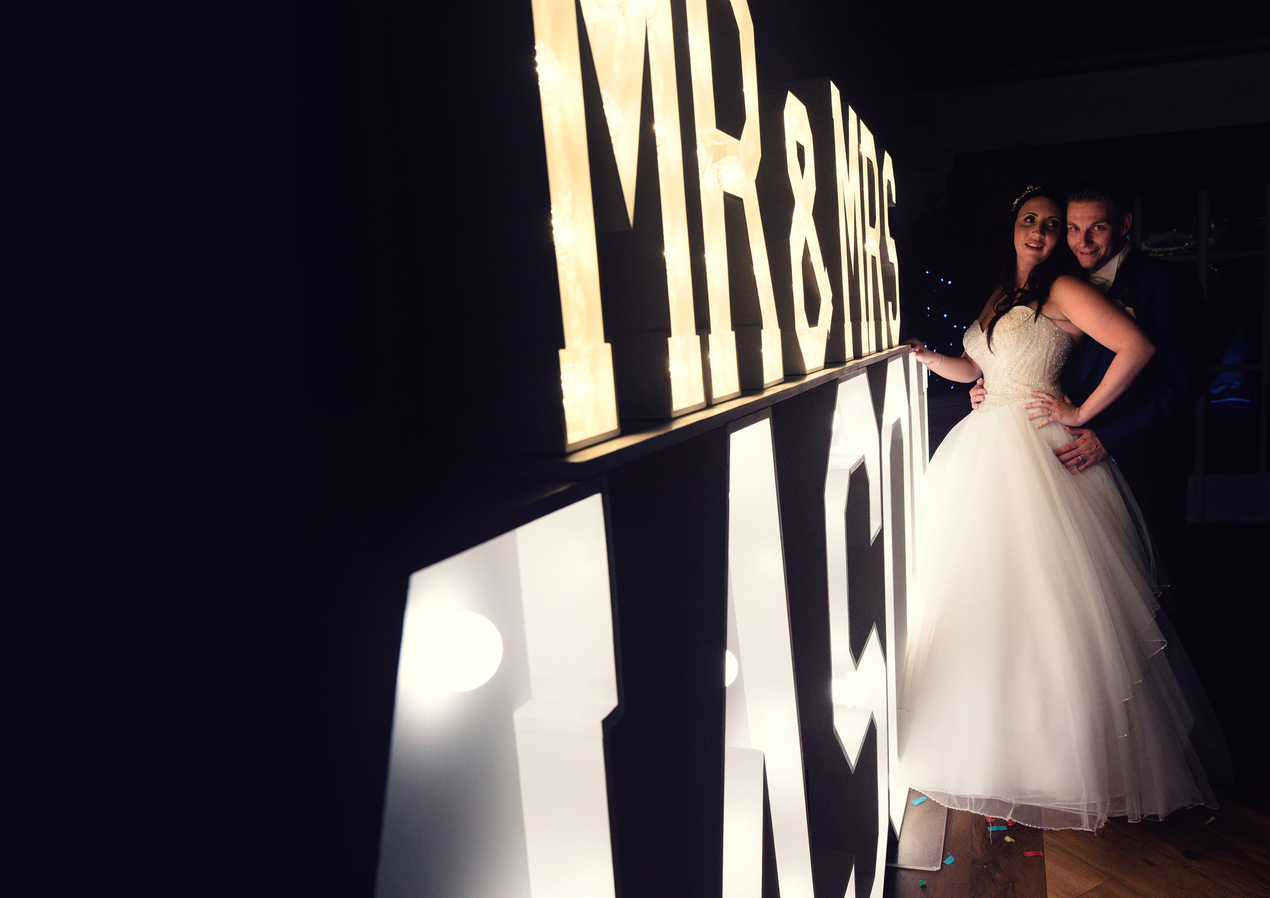 The bride and groom with their name in lights