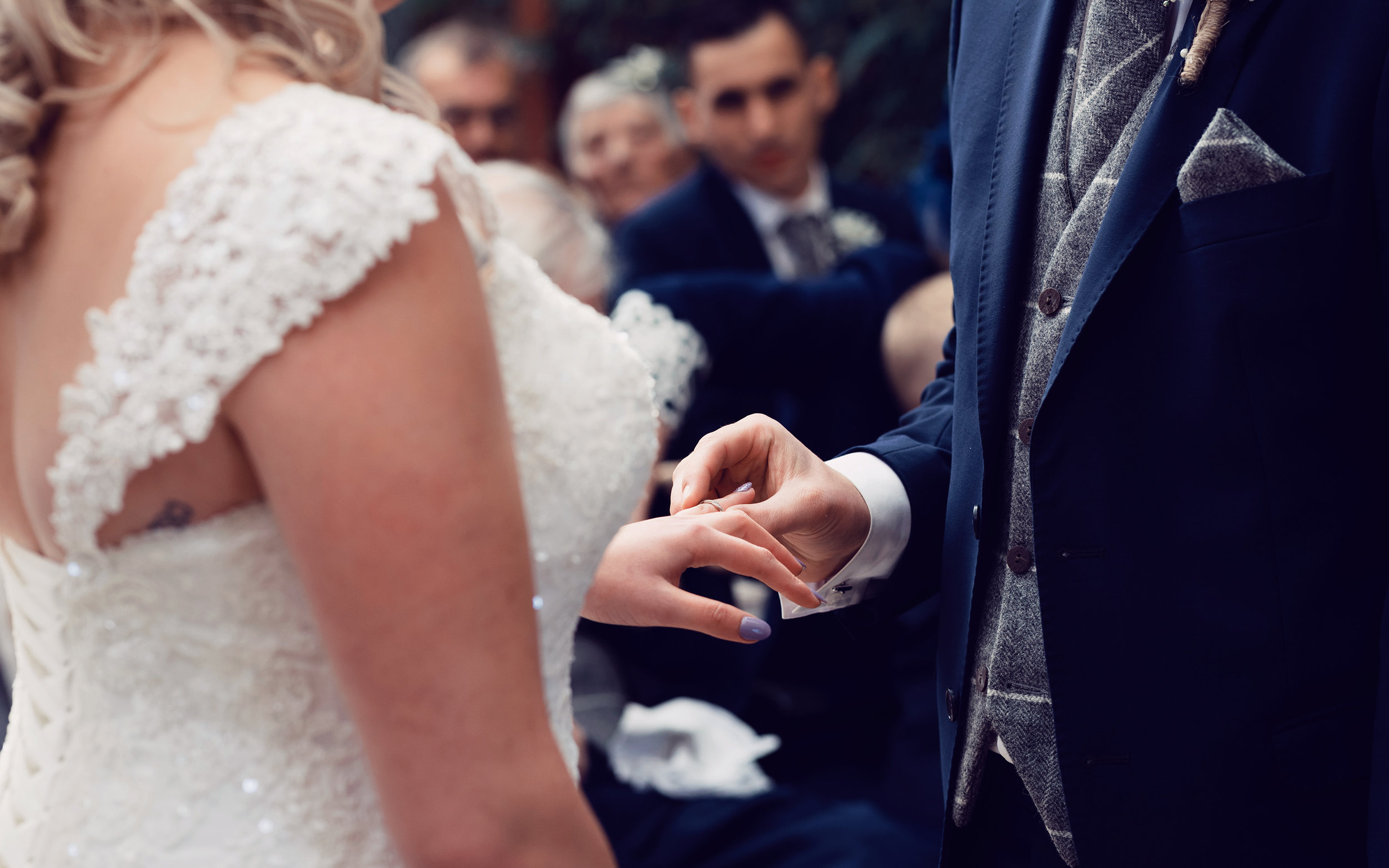 The happy couple exchanging wedding rings