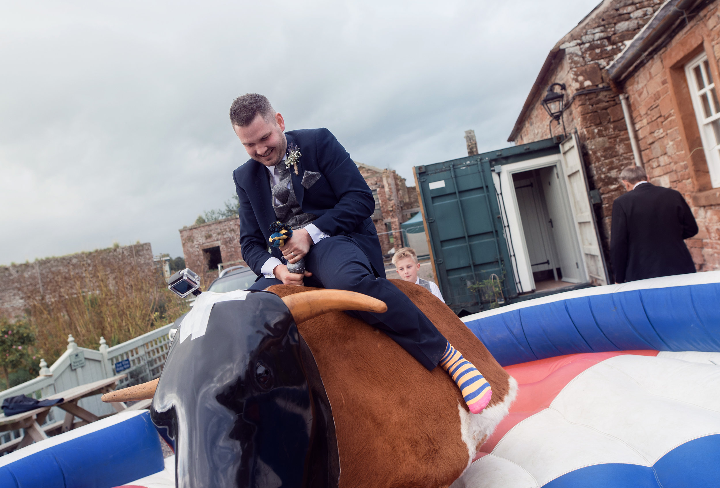 The groom doing his best to stay on the rodeo bull ride he did not last very long at all