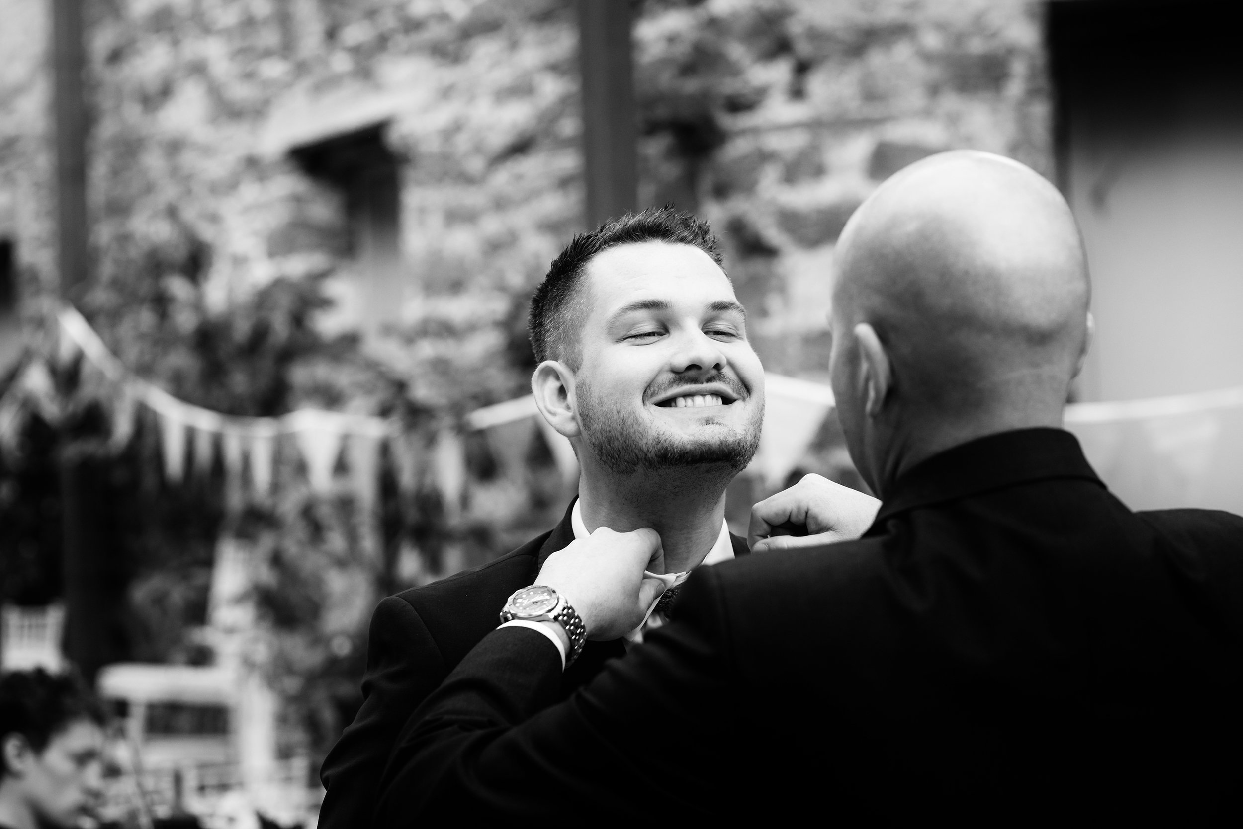 The groom getting a little help to straighten his tie