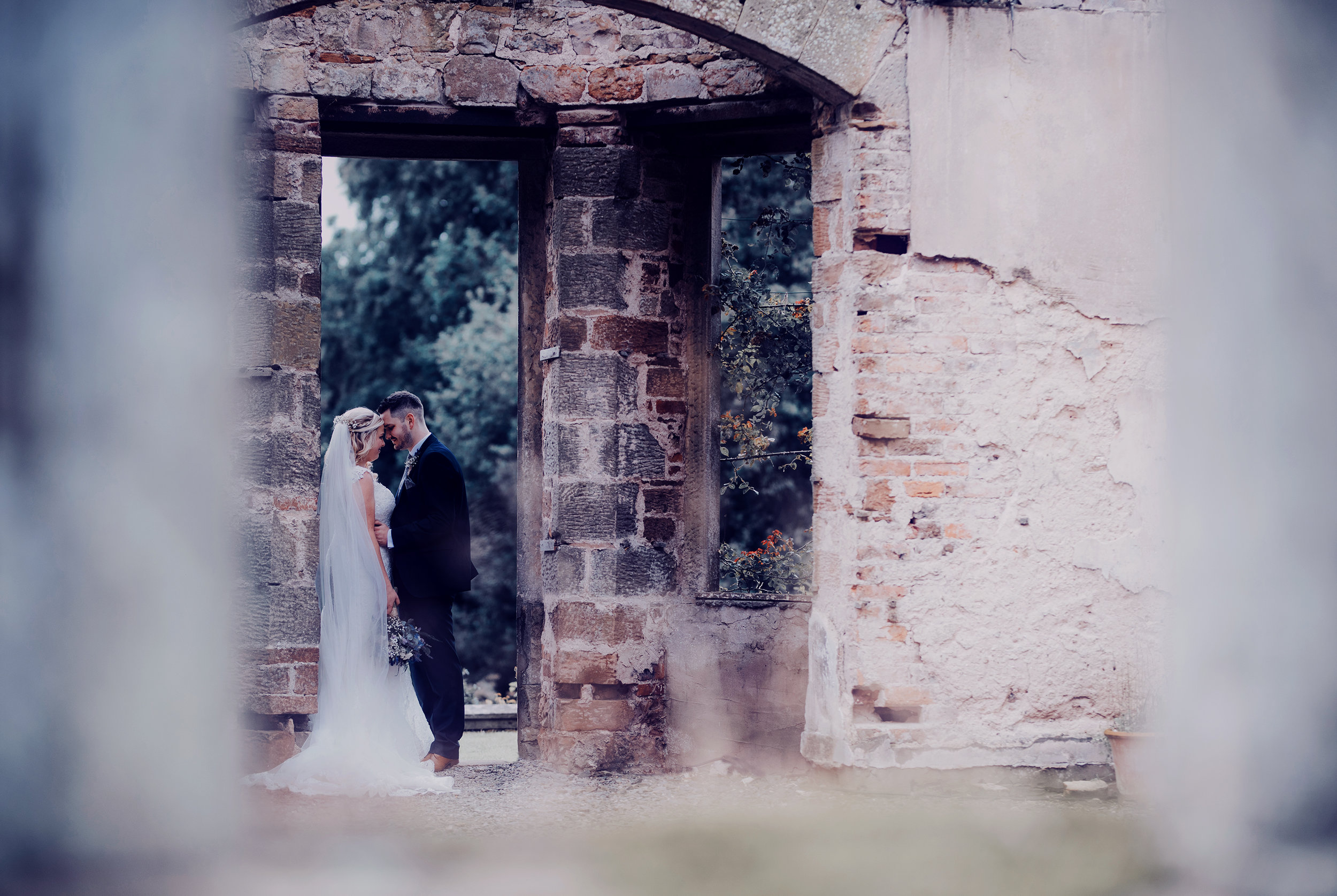 Bride and groom standing in a doorway Kirklinton Hall
