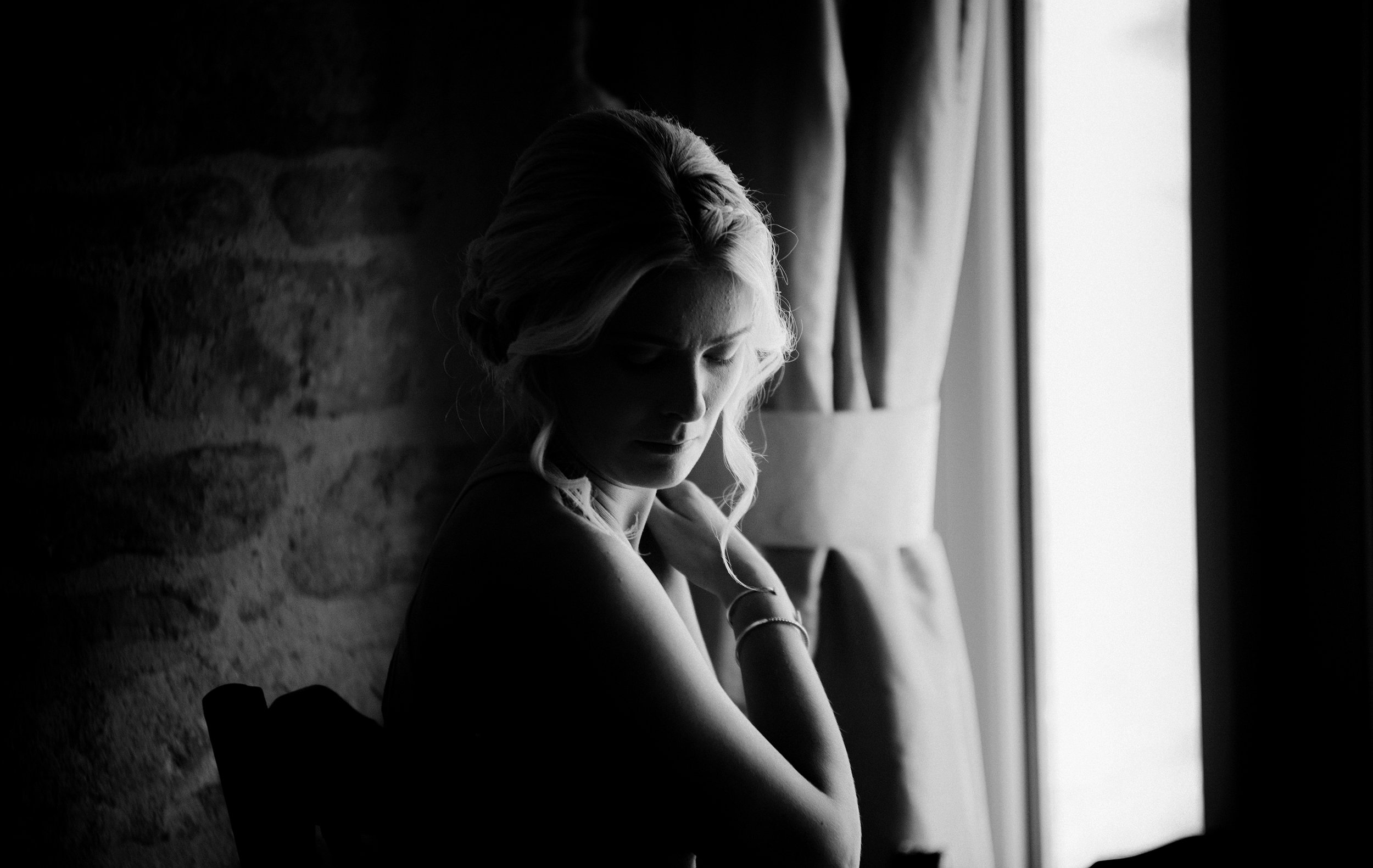 Beautiful black and white moody images of a bridesmaid in the window light