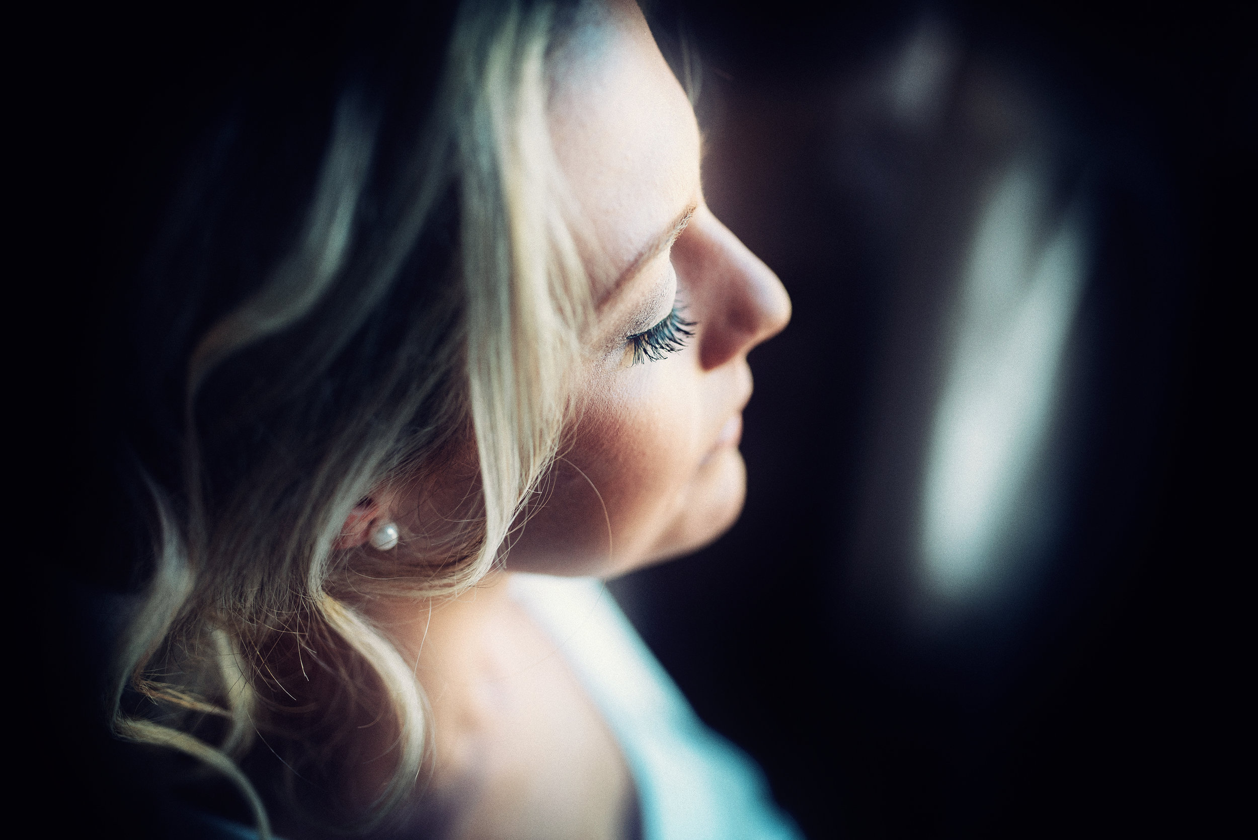 A bridesmaid in subdued light during bridal preparations