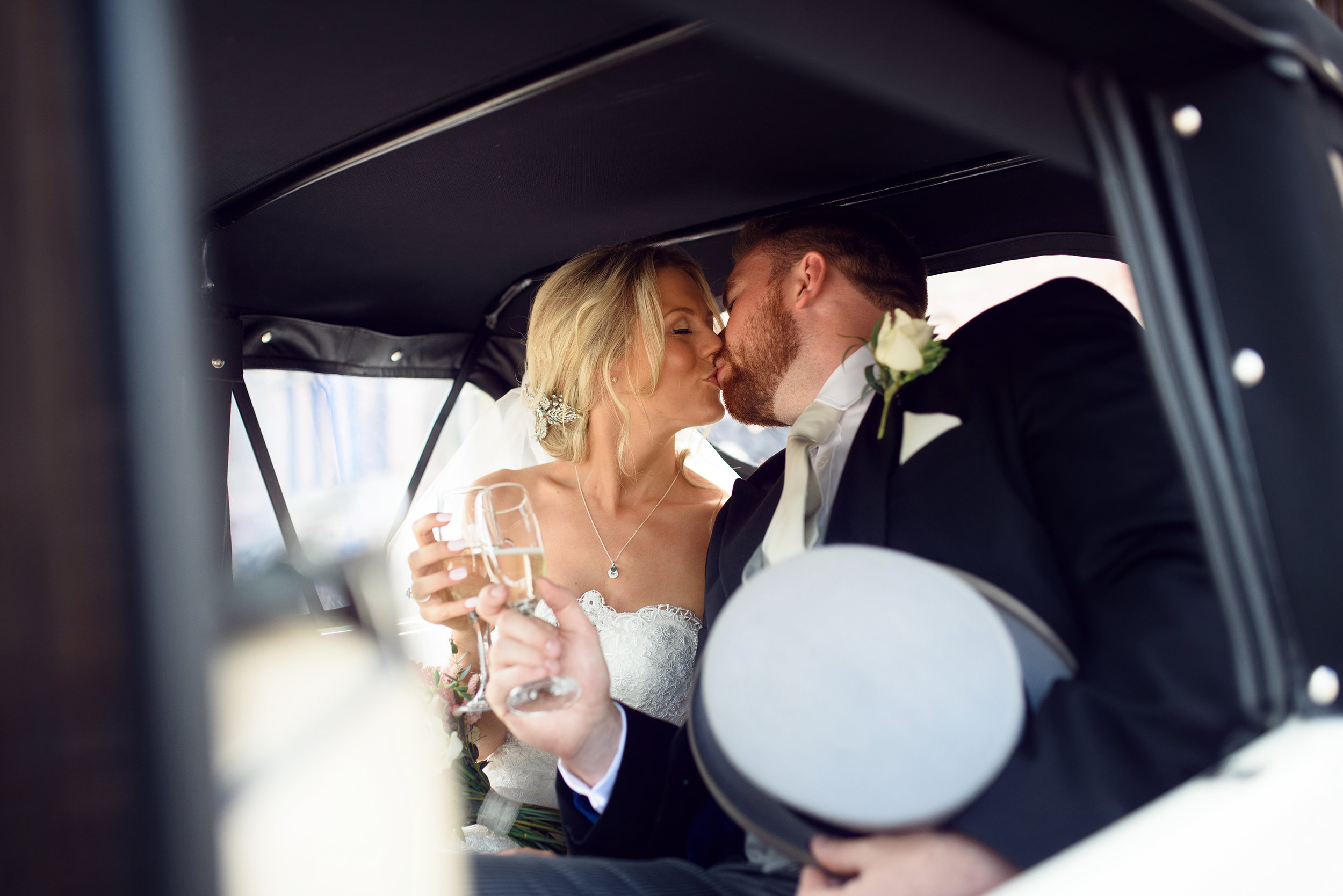 The bride and groom kissing in the back of the car