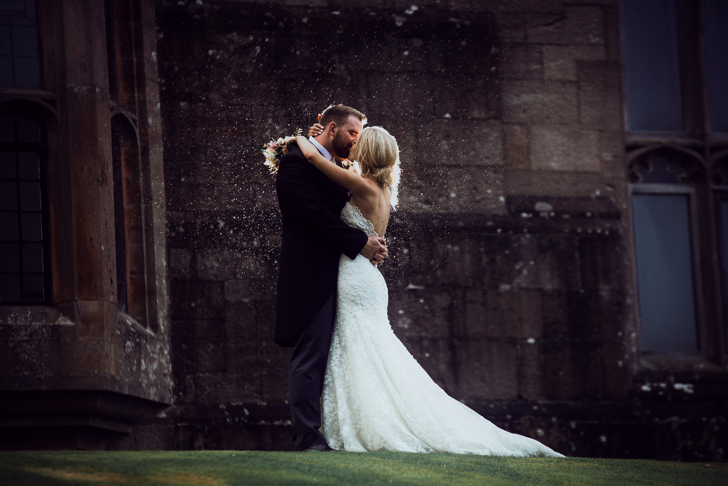 The bride and groom kissing in the rain