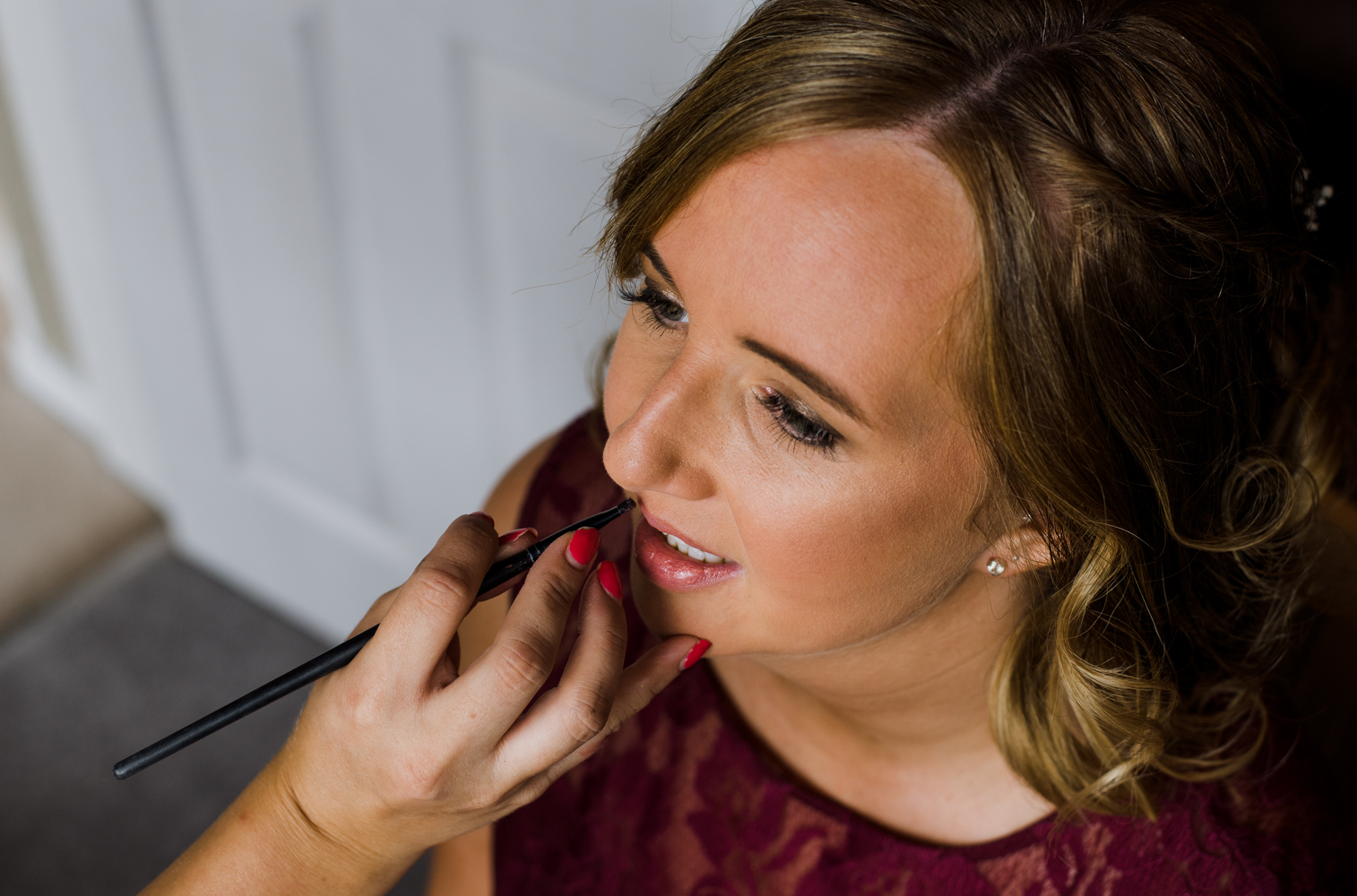 A bridesmaid having her lipstick applied during morning preparations
