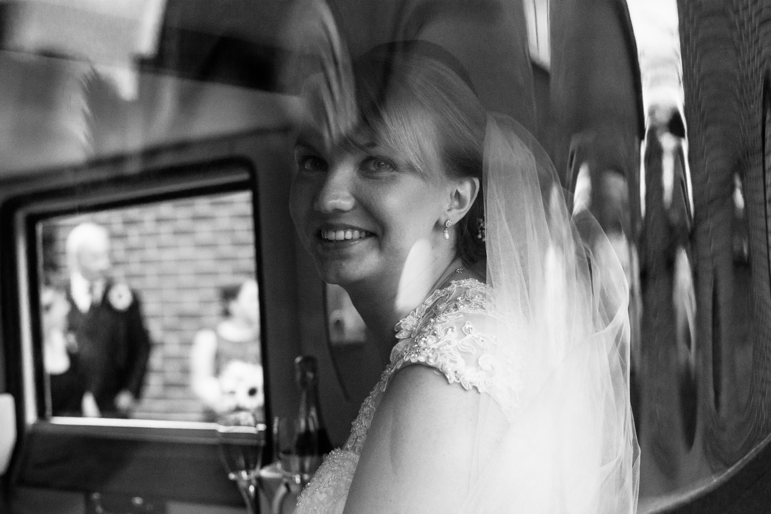 Black and white images of the bride sitting in the back of the wedding car shot through a glass window